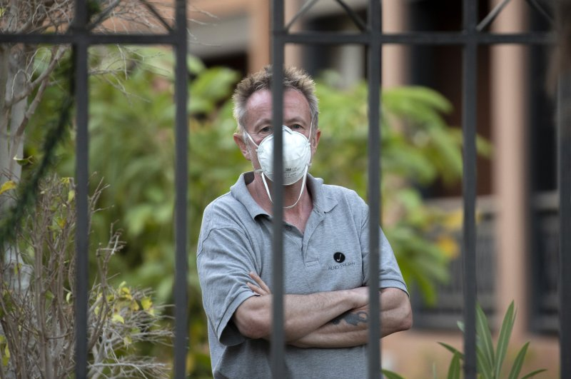 A man wearing a face mask looks out from the H10 Costa Adeje Palace hotel in La Caleta, in the Canary Island of Tenerife, Spain, Friday Feb. 28, 2020. (AP Photo)