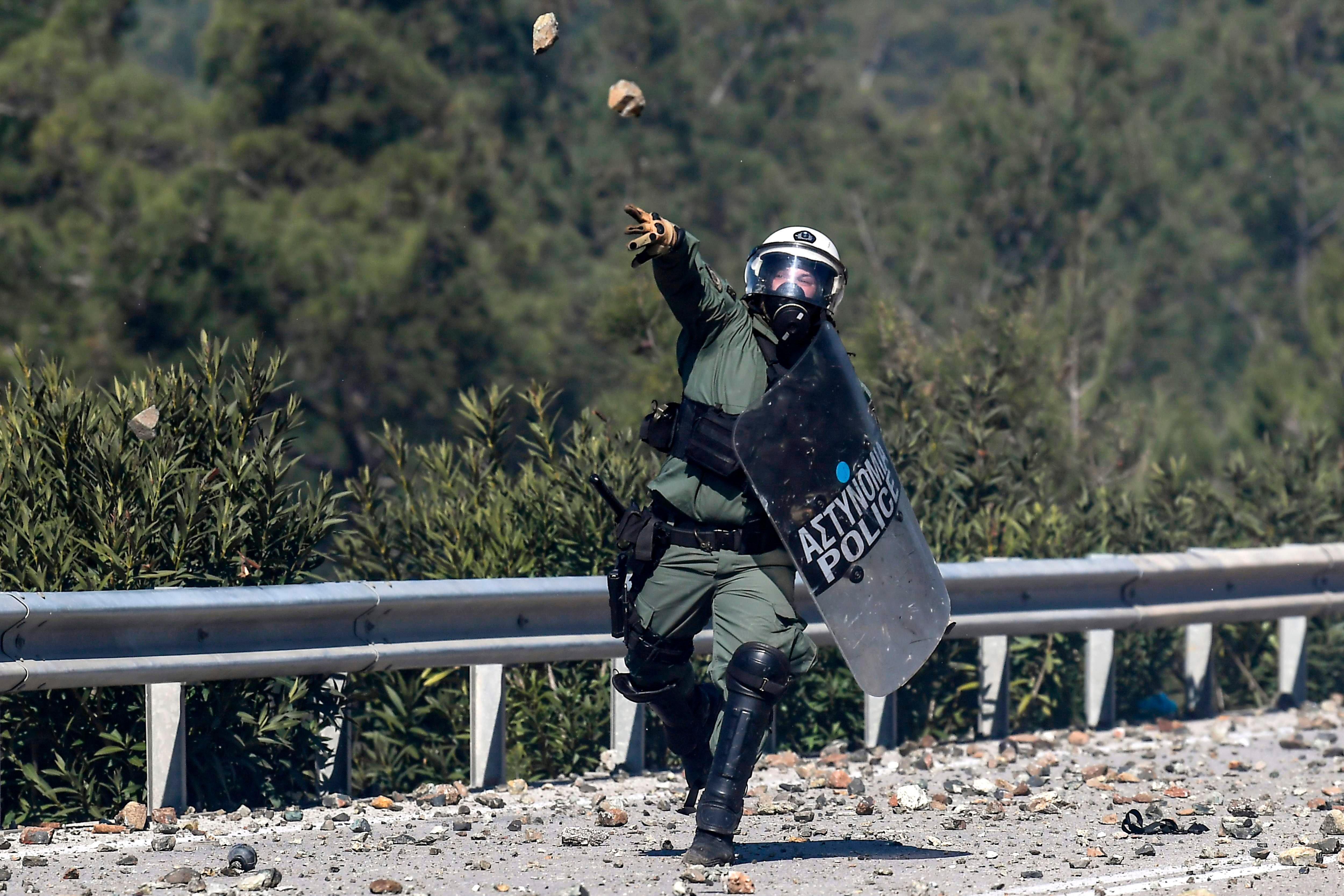 TOPSHOT - A Greek anti-riot officer lobs a stone back at demonstrators during clashes against the construction of a new controversial migrant camp near the town of Mantamados on the northeastern Aegean island of Lesbos, on February 26, 2020. - The Greek islands of Lesbos, Chios and Samos staged a general strike on February 26, as protests against the construction of new migrant camps intensified. For a second day, protesters on Lesbos faced off against riot police near the town of Mantamados, close to the site of a planned camp for up to 7,000 people. Small groups of protesters threw stones and firebombs at the police, who responded with tear gas and flash grenades. (Photo by ARIS MESSINIS / AFP)