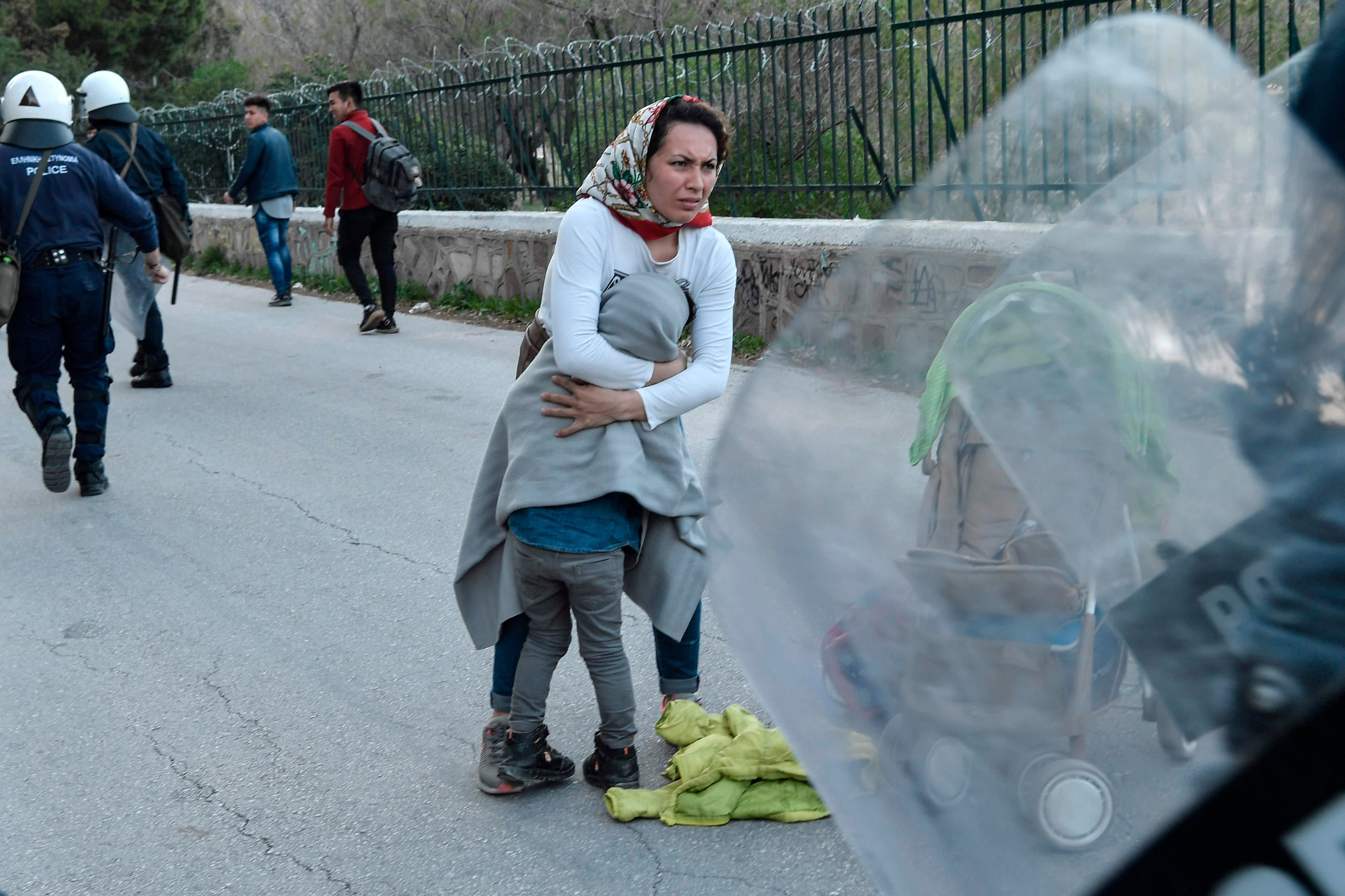 TOPSHOT - A woman protects her child, while police dispearses migrants who have gathered outside the port of Mytilene, on the island of Lesbos hoping to get on a ferry to Athens on March 3, 2020. - Several aid groups on Greece's Lesbos said they were suspending work with refugees and evacuating staff on March 3 in the wake of violence and threats, as tensions soar on an island in the crosshairs of the migrant crisis. EU chiefs pledged millions of euros of financial assistance to Greece to help tackle the migration surge. (Photo by LOUISA GOULIAMAKI / AFP)