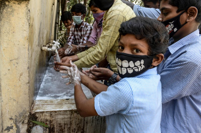 Students wearing facemasks wash their hands before attending a class at a governement-run high school in Secunderabad, the twin city of Hyderabad, on March 4, 2020, as part of health measures taken against the COVID-19 coronavirus outbreak. (AFP Photo)