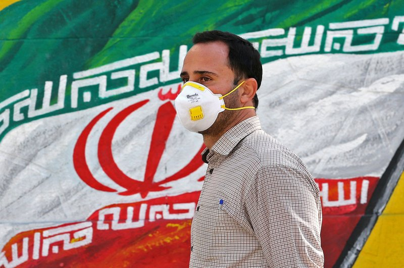 Man wearing a face mask walks past a mural of Iran's national flag in Tehran, Iran, March 4, 2020. (AFP Photo)