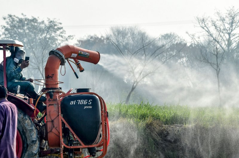Agriculture Department officials spray pesticides from a tractor to kill locusts in a field in Pipli Pahar village, Pakistan, Feb. 23, 2020. (AFP Photo)