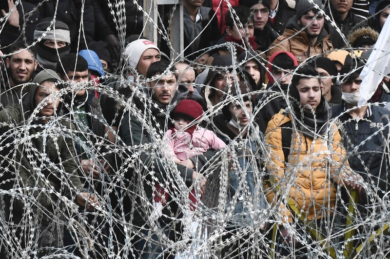 This picture taken from the Greek side of the Greece-Turkey border near Kastanies, shows migrants waiting on the Turkish side on March 2, 2020. (AFP Photo)