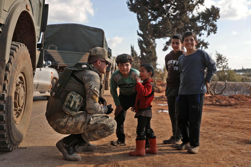 A Turkish soldier speaks to displaced Syrians near the town of Batabu on the highway linking Idlib to the Syrian Bab al-Hawa border crossing with Turkey, on March 2, 2020. (AFP Photo)