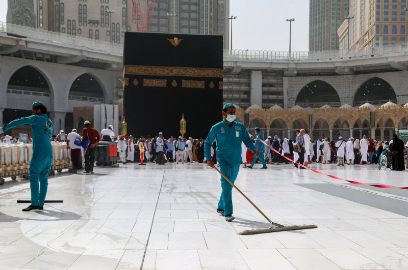 Cleaners wear protective face masks following the outbreak of the coronavirus, as they swipe the floor at the Kaaba in the Grand Mosque in the holy city of Mecca, Saudi Arabia, March 3, 2020. (Reuters Photo)