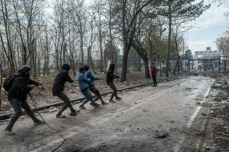 Migrants try to remove fences during the clashes with Greek police, after they tried to pass on the Greek side, on the buffer zone near Pazarkule crossing gate in Edirne, Turkey, on March 4, 2020. (AFP Photo)
