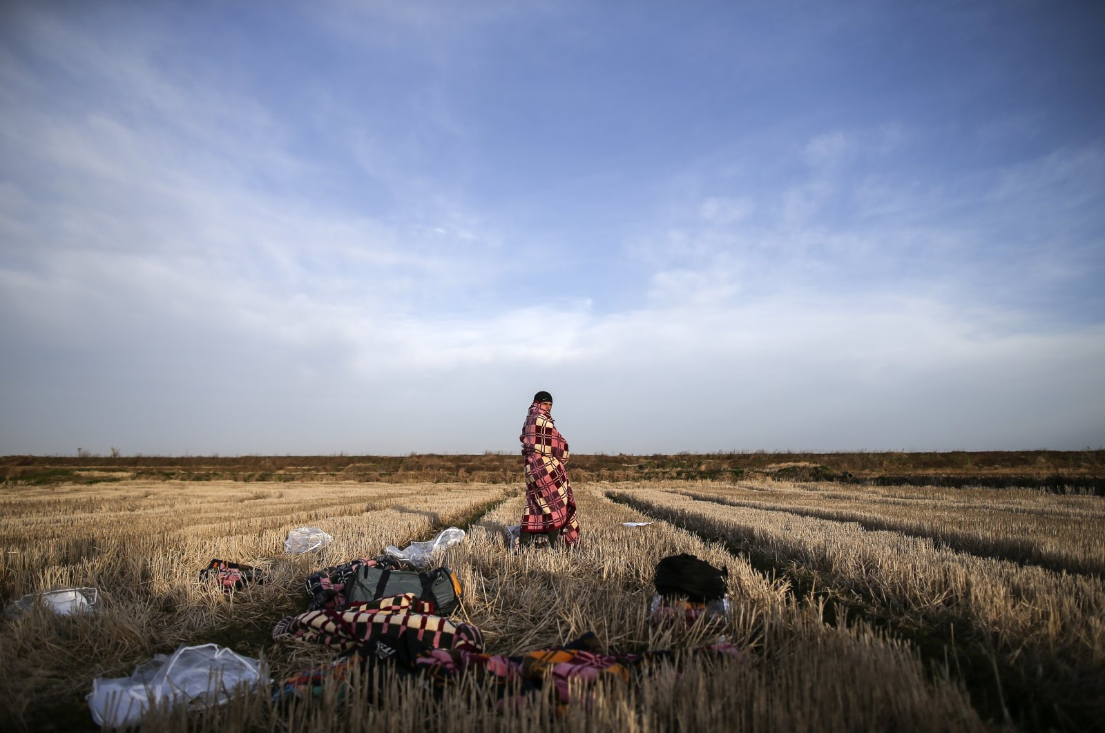 A migrant uses a blanket to warm himself in a field near Edirne, at the Turkish-Greek border, March 3, 2020. (AP Photo)