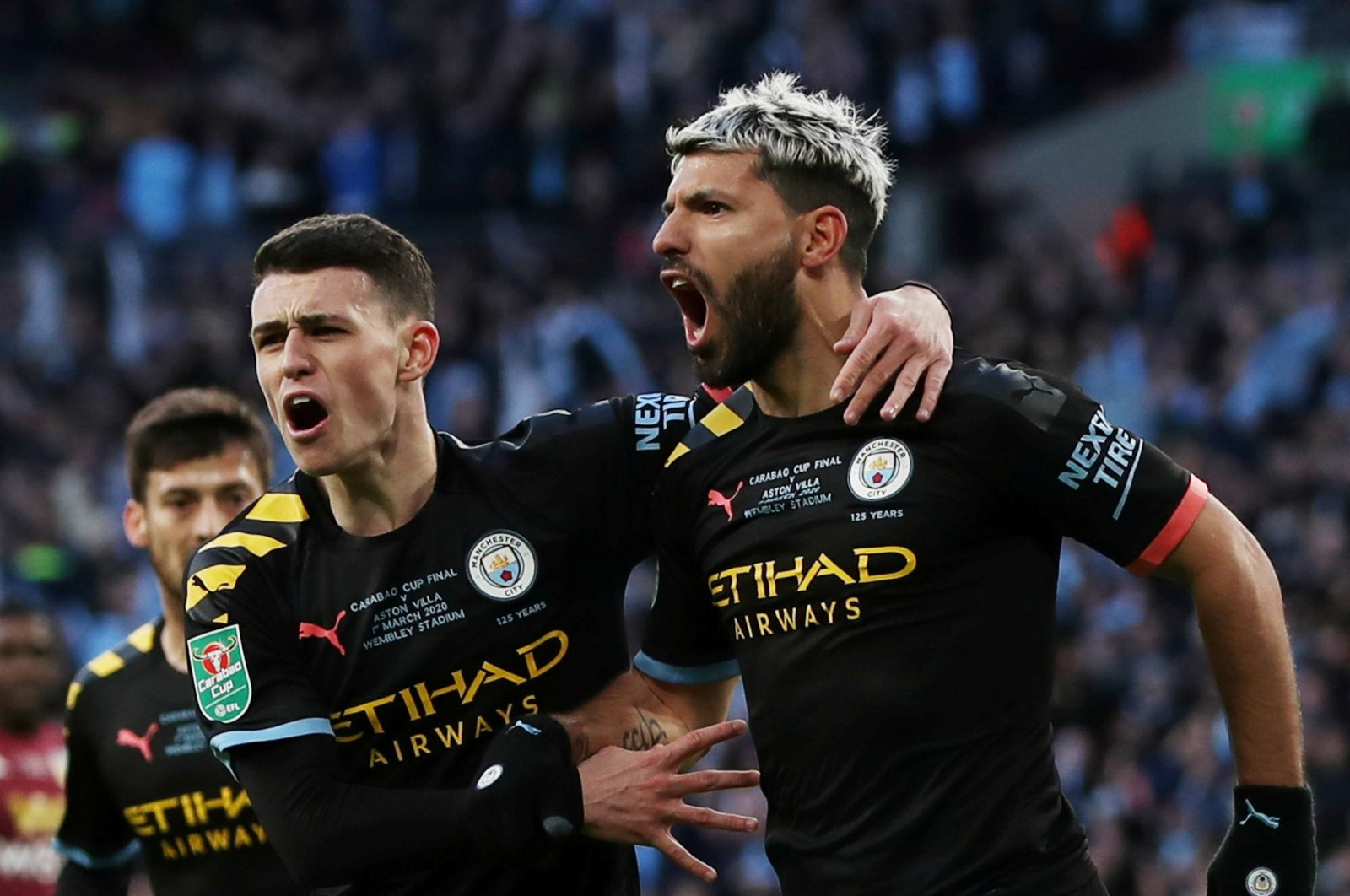 Manchester City's Sergio Aguero (R) and Phil Foden celebrate scoring their first goal against Aston Villa in London, March 1, 2020. (Reuters Photo)