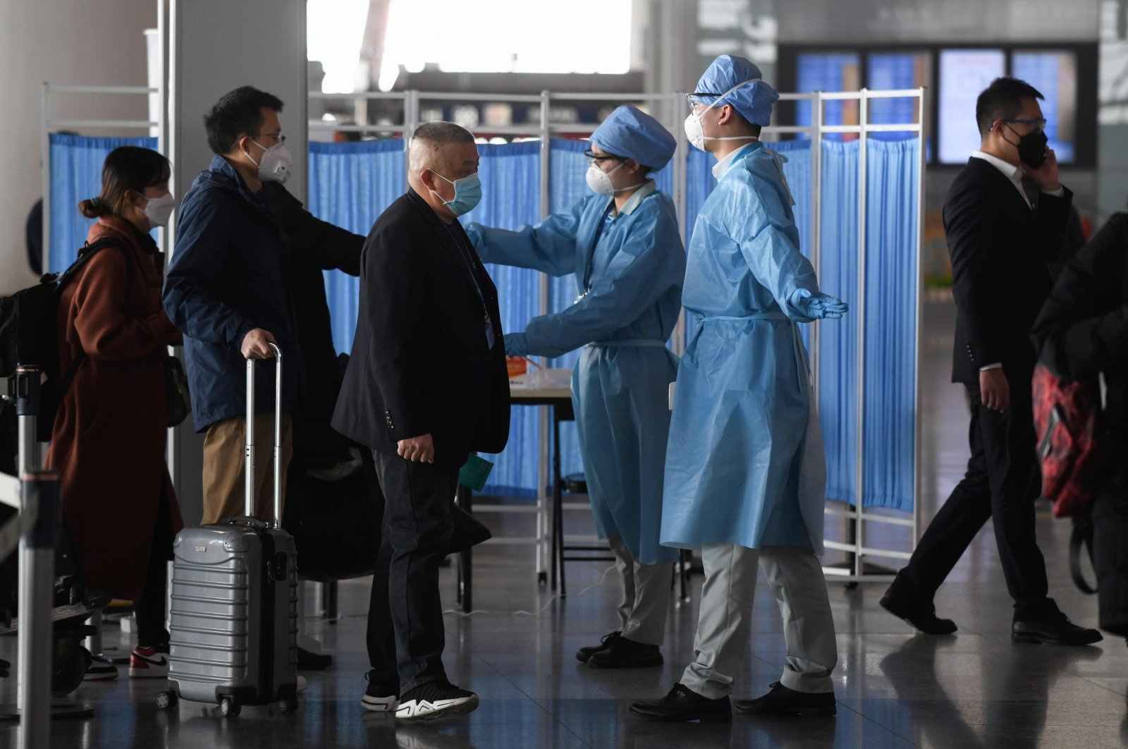 Workers wearing protective clothing (R) check the temperatures of passengers arriving at the Beijing Capital Airport in Beijing on March 5, 2020. (AFP Photo)