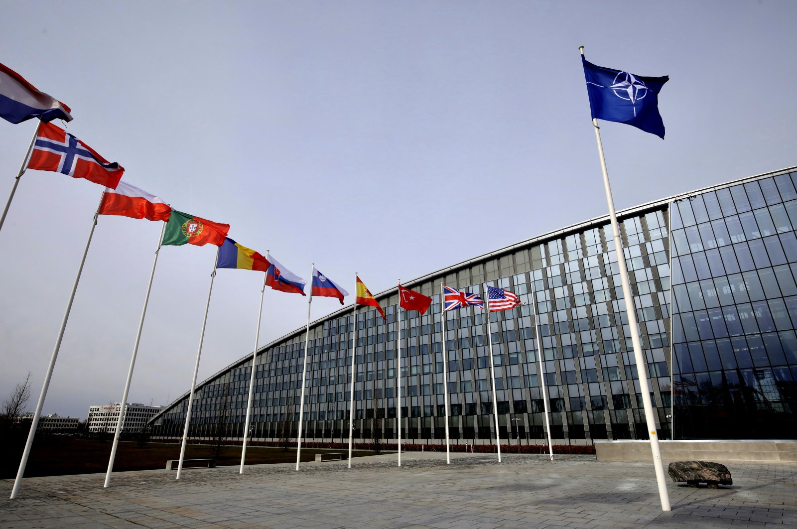 Flags of Alliance members flap in the wind outside NATO headquarters in Brussels, Feb. 28, 2020. (AP Photo)