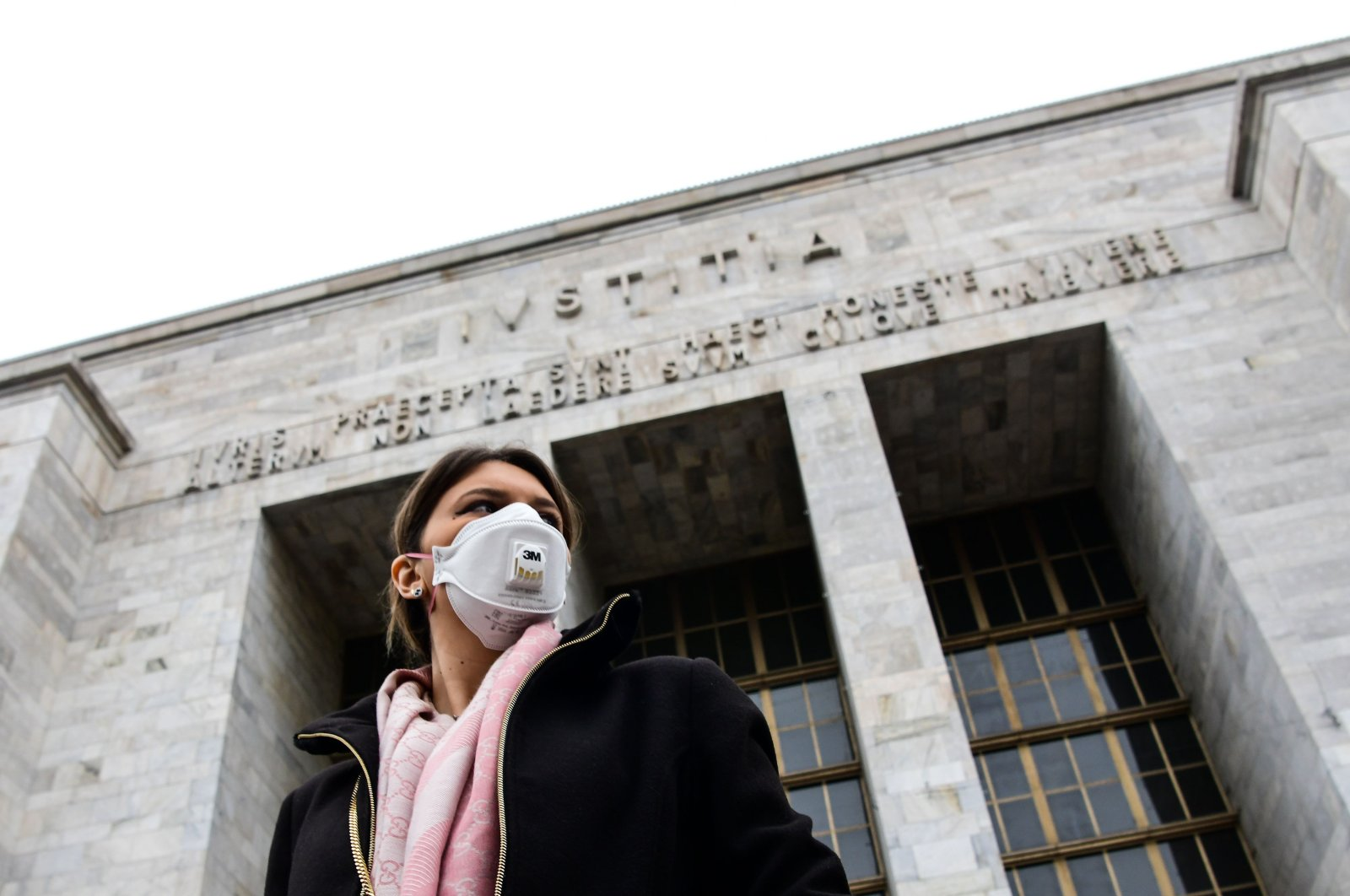 A woman wearing a respiratory mask exits from the Palace of Justice in Milan, on March 5, 2020. (AFP Photo)