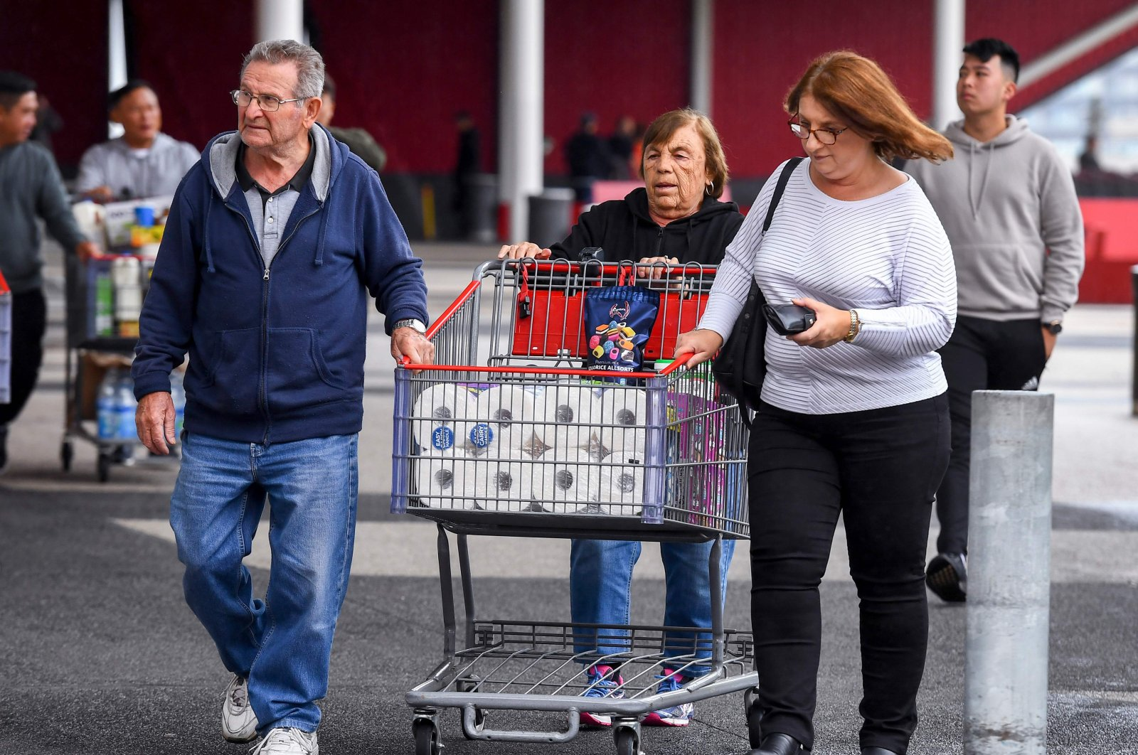 People leave a Costco warehouse with rolls of toilet paper amongst their groceries in Melbourne on March 5, 2020. (AFP Photo)