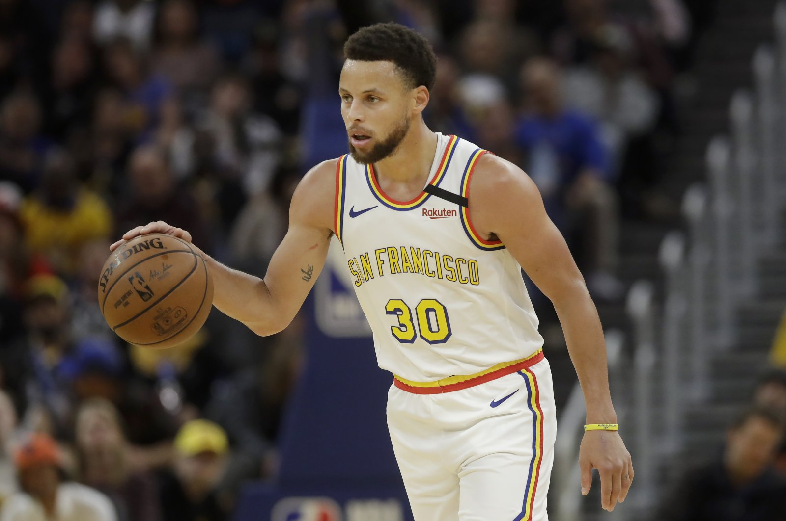 Golden State Warriors guard Stephen Curry (30) dribbles the ball up the court against the Toronto Raptors during the second half of an NBA basketball game in San Francisco, Thursday, March 5, 2020. (AP Photo)