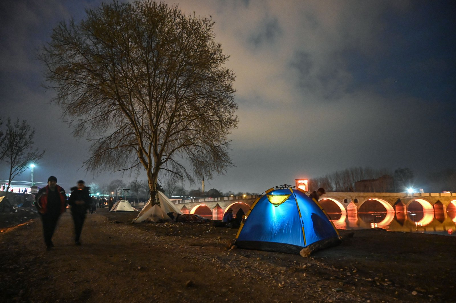Migrants spend the night in a makeshift camp on the bank of the Tunca river as they try to enter Europe at the Turkey-Greece border, near the Pazarkule crossing gate in Edirne, March 5, 2020. (AFP Photo)