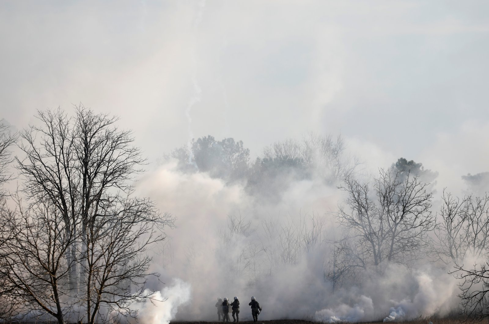 Greek riot police are seen through smoke during clashes at the Greek-Turkish border in Kastanies, Evros region, Friday, March 6, 2020. (Reuters Photo)