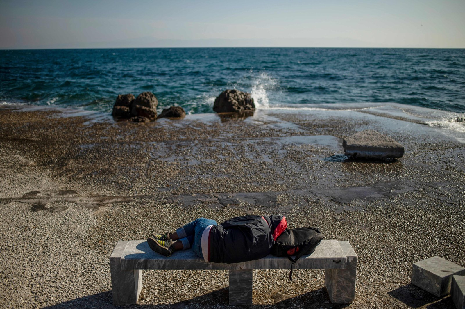 A migrant sleeps on a bench at the harbor quay on the island of Lesbos, Greece, on March 3, 2020 (AFP Photo)