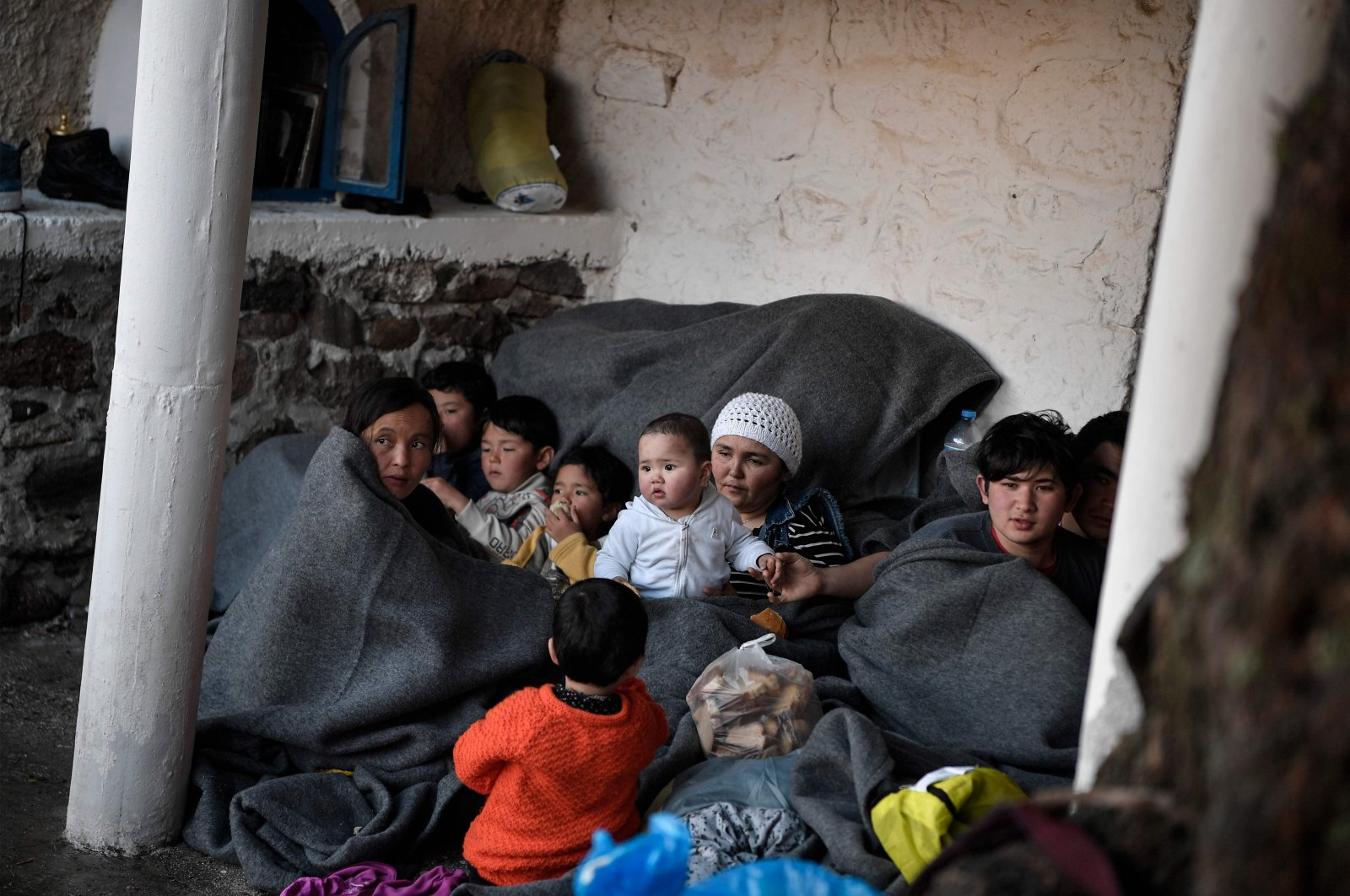 Migrants and refugess who arrived from Turkey to the Greek island of Lesbos on March 5, try to keep warm as they gather in the yard of a small church where they have spent the rainy night near Skala Sykamnias on March 6, 2020. (AFP Photo)