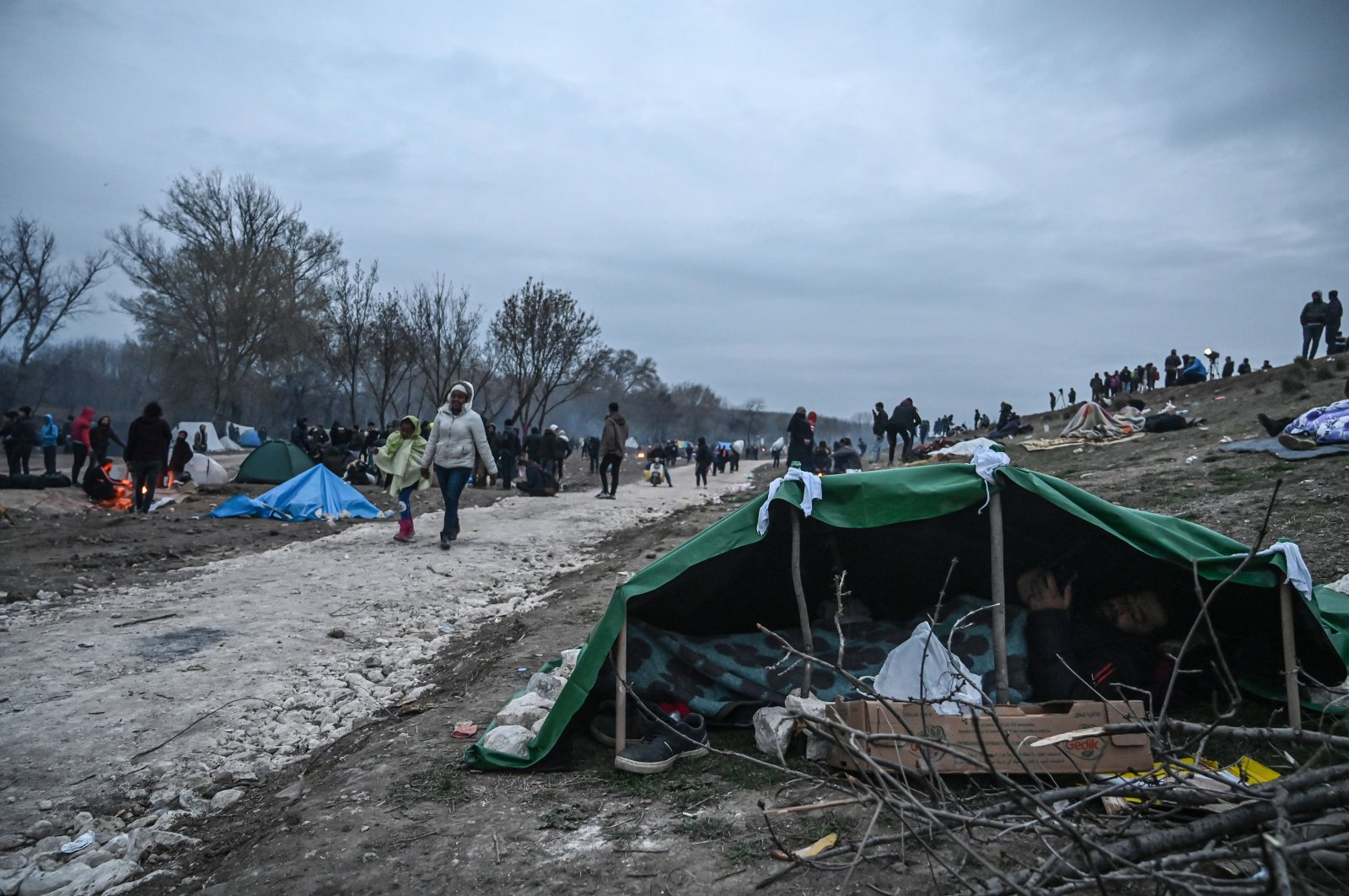 A migrant rests under a makeshift tent near the Tunca river as migrants and refugees wait to resume their efforts to cross the Greek border near the Pazarkule border gate in the city of Edirne, northwestern Turkey, on March 5, 2020. (AFP Photo)