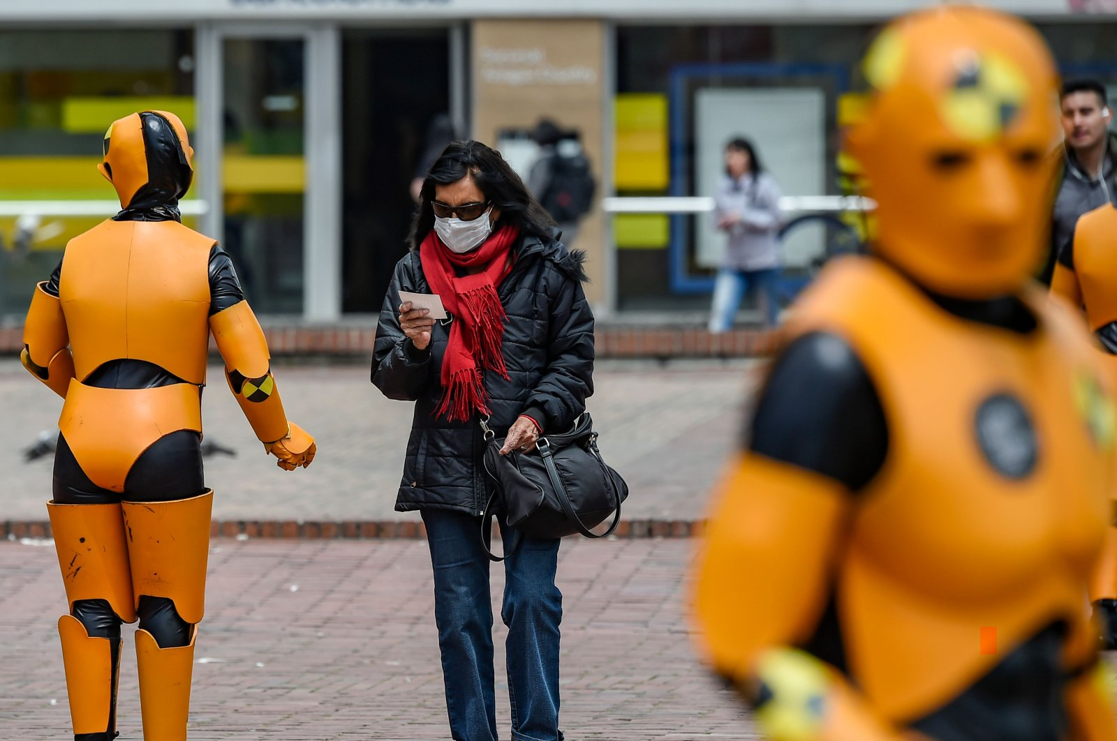 A woman wearing a protective face mask as a precaution against the spread of the new coronavirus, the COVID-19, walks by traffic personnel in road safety robot suits, in Bogota on March 6, 2020. (AFP Photo)