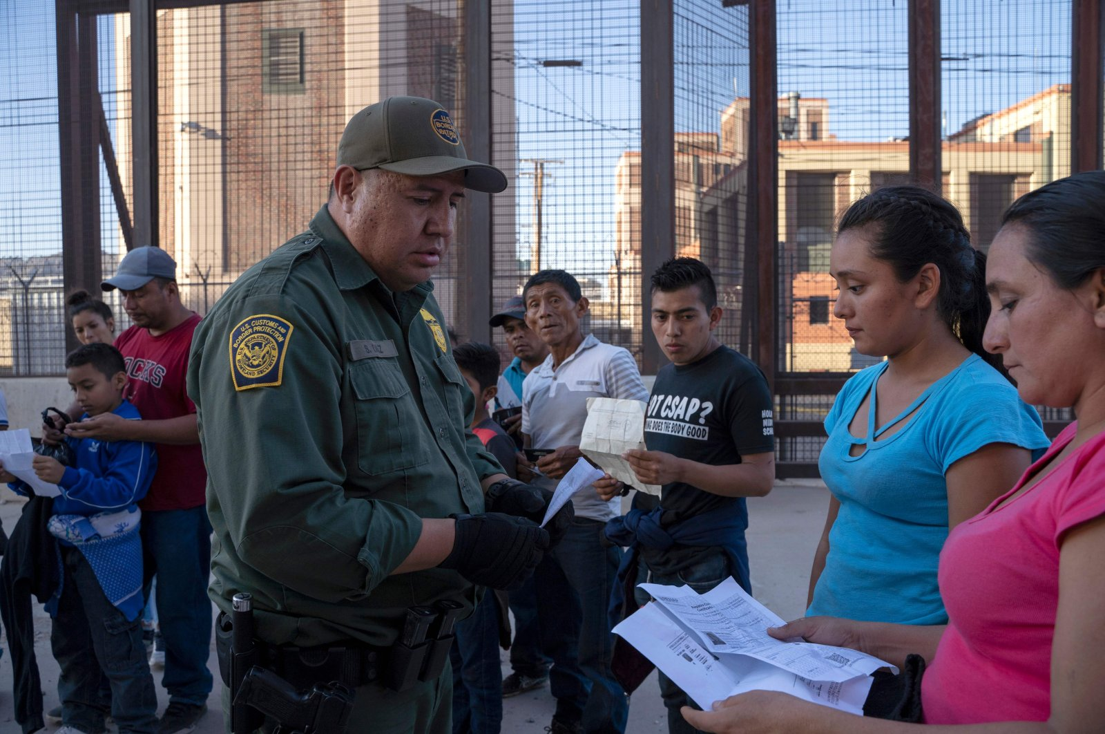 In this file photo taken on May 16, 2019, U.S. Customs and Border Protection agent checks documents of a small group of migrants, who crossed the Rio Grande from Juarez, Mexico, in El Paso, Texas. (AFP)