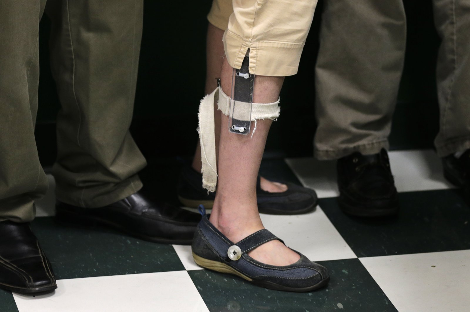 In this Aug. 13, 2014 photo, a female student wearing a shocking device on her leg lines up with classmates after lunch at the Judge Rotenberg Educational Center in Canton, Mass. (AP Photo)