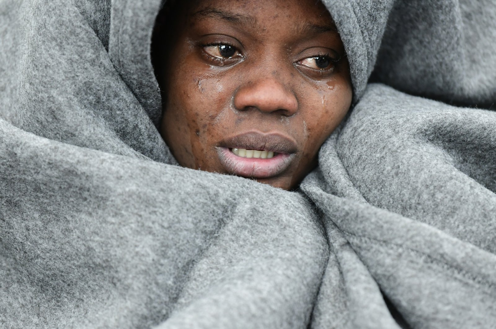 A migrant woman cries as she tries to warm herself upon the arrival of migrants at the village of Skala Sikaminias, on the Greek island of Lesbos, after crossing the Aegean sea from Turkey, Saturday, Feb. 29, 2020. (AP Photo)