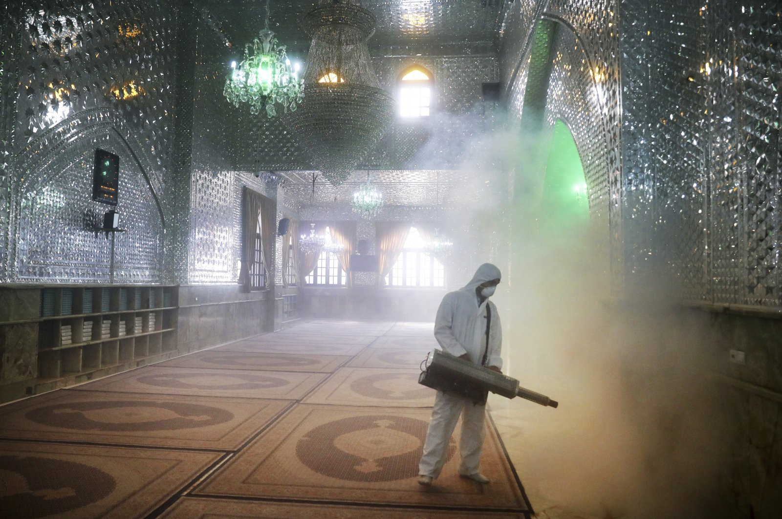 A firefighter disinfects the shrine of Saint Saleh to help prevent the spread of the new coronavirus in northern Tehran, Iran, Friday, March, 6, 2020. (AP Photo)