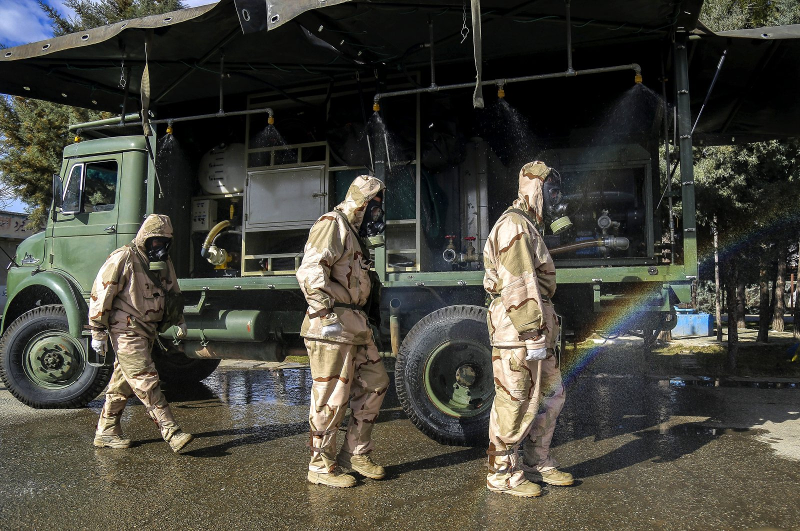 In this Sunday, March 1, 2020 photo, Revolutionary Guard members take part in disinfecting the city to help prevent the spread of the new coronavirus in Sanandaj, western Iran. (Tasnim News Agency via AP)