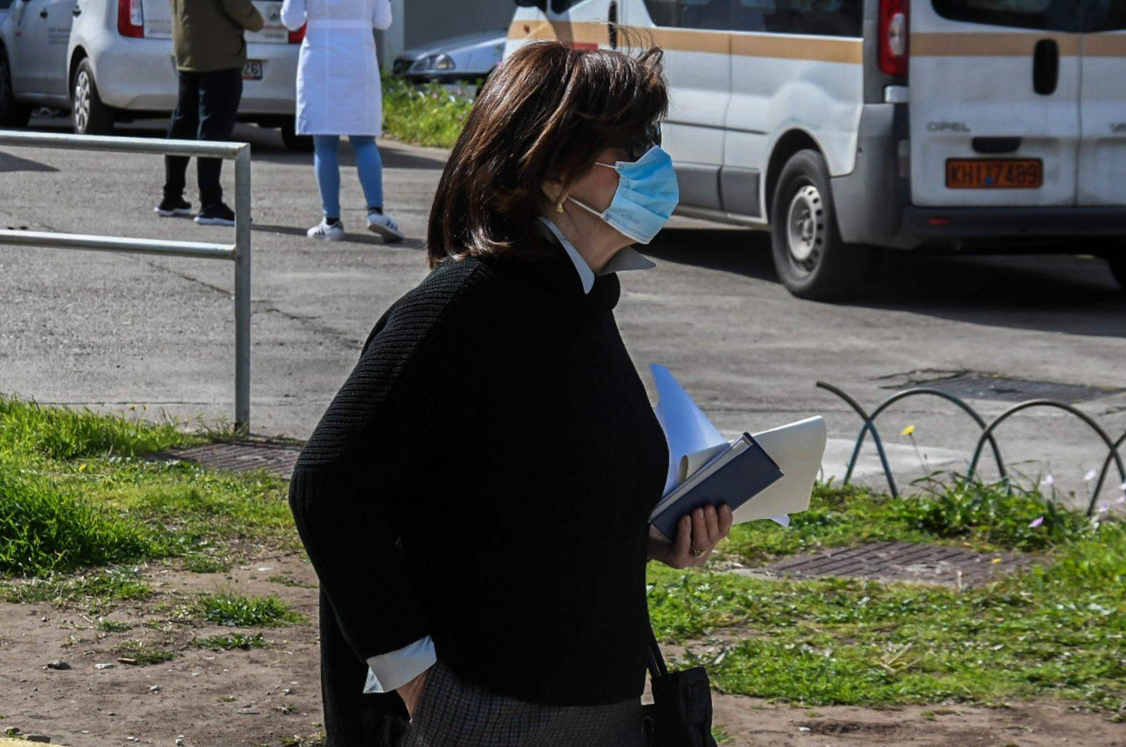 A woman wearing a protective face mask walks in front of the Patras University Hospital in Rio, outside Patras, southwestern Greece, where three patients infected with COVID-19, the new coronavirus, are hopitalised.