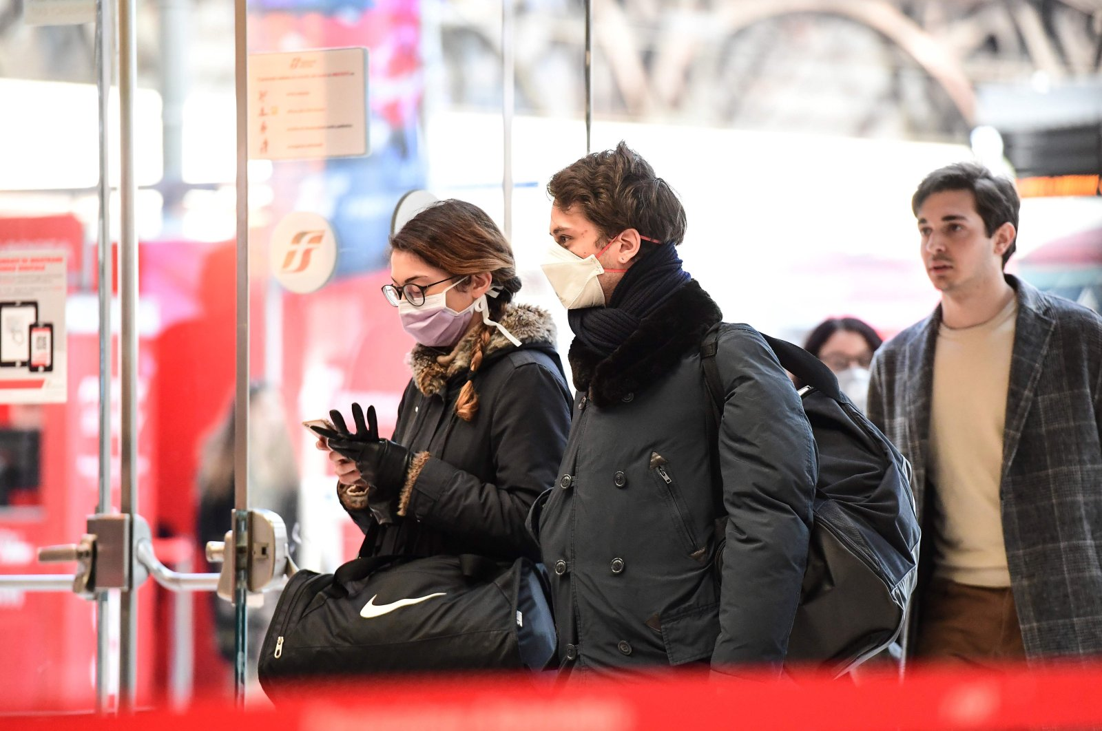 Passengers wearing protective face masks enter Milano Centrale railway station in Milan on March 8, 2020. (AFP Photo)