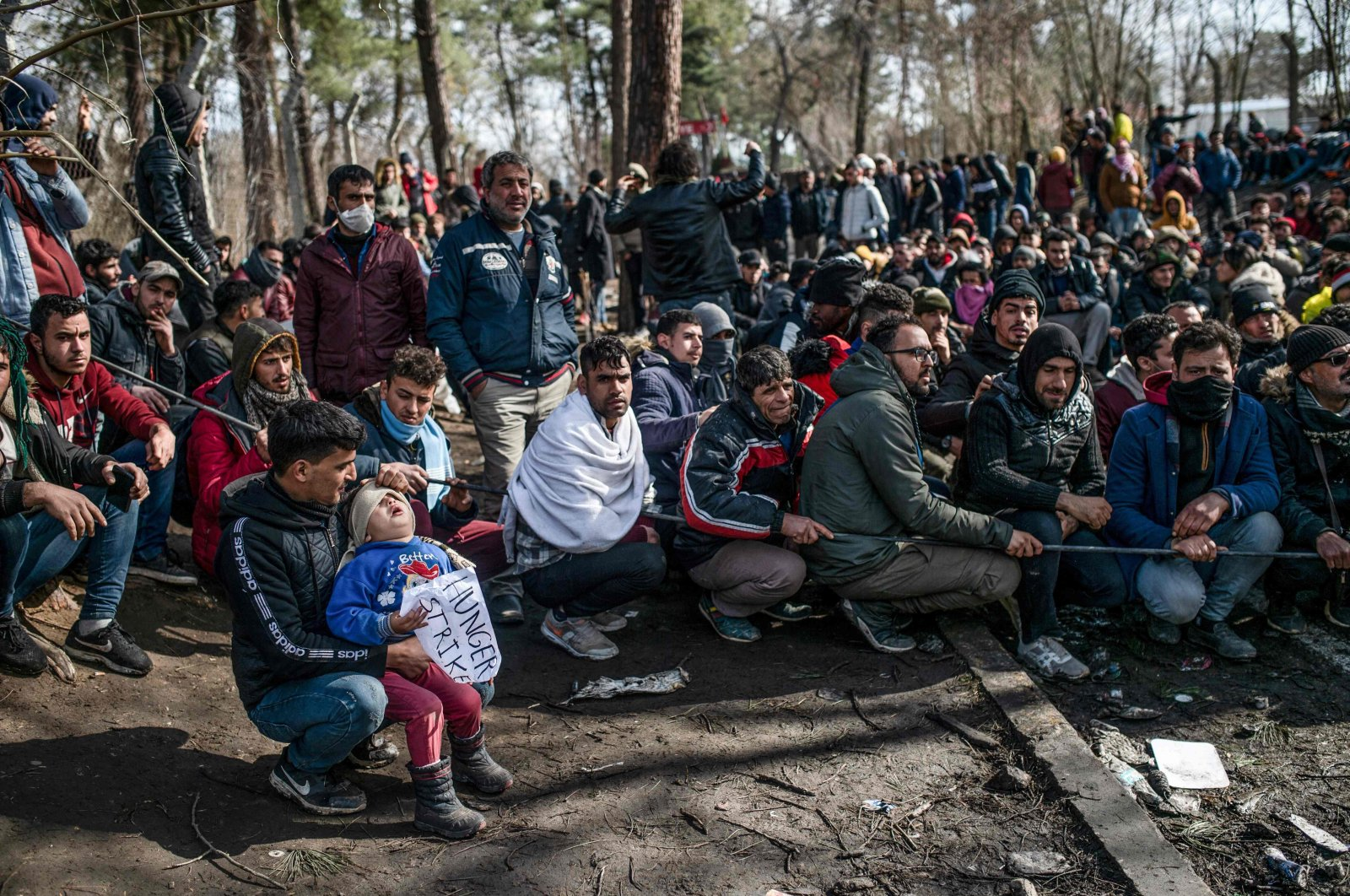 Migrants wait with their children in the buffer zone at the Turkey-Greece border near the Pazarkule crossing gate in Edirne, Mar. 5, 2020. (AFP Photo)