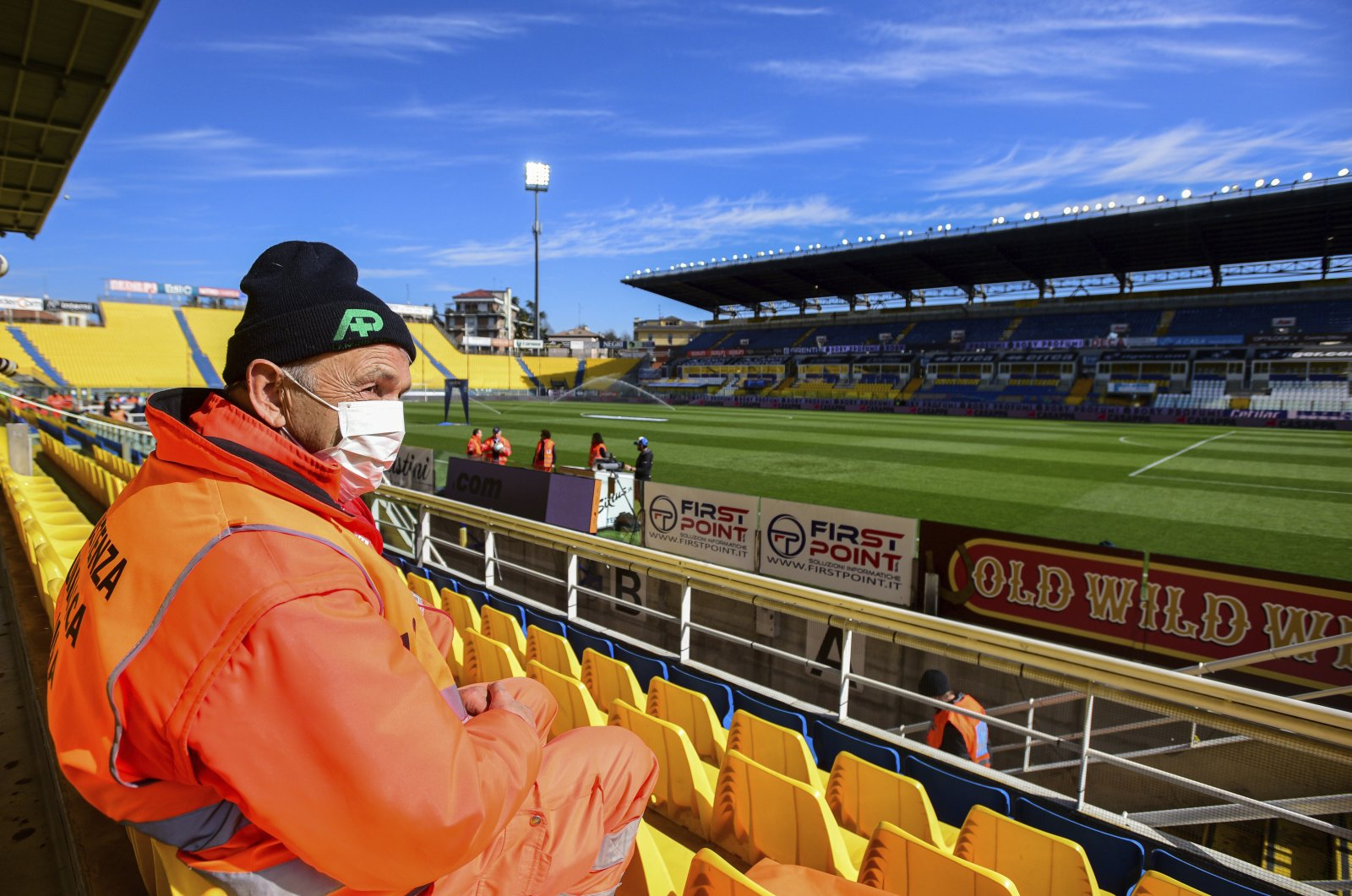 A man with a mask sits in the stands ahead of a Serie A match between Parma and Spal, March 8, 2020. (AP Photo)