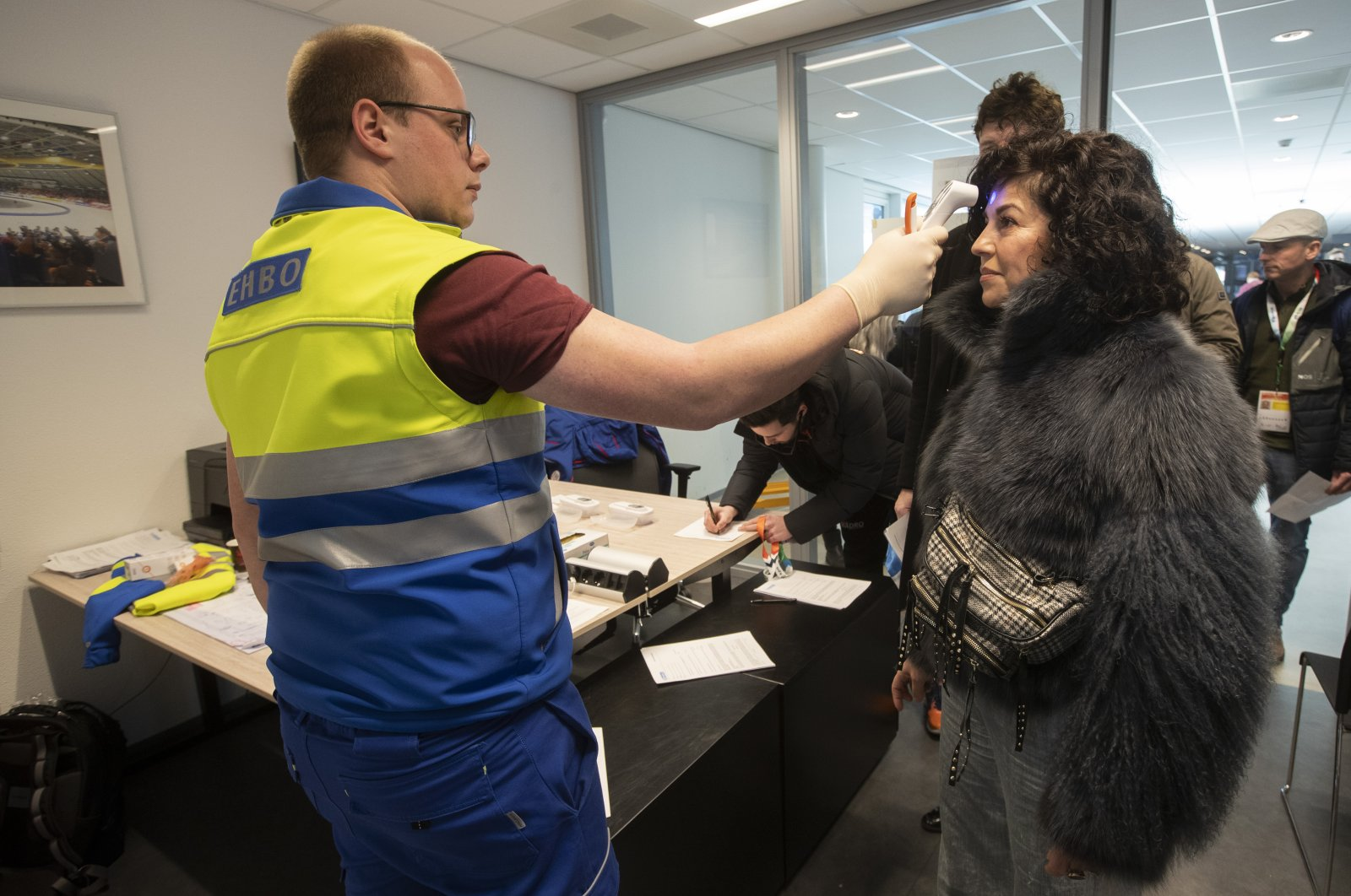 A medical team member checks an accredited person's body temperature and checks for possible symptoms of the coronavirus prior to the final of World Cup speedskating at the Thialf ice arena in Heerenveen, northern Netherlands, Saturday, March 7, 2020. (AP Photo)