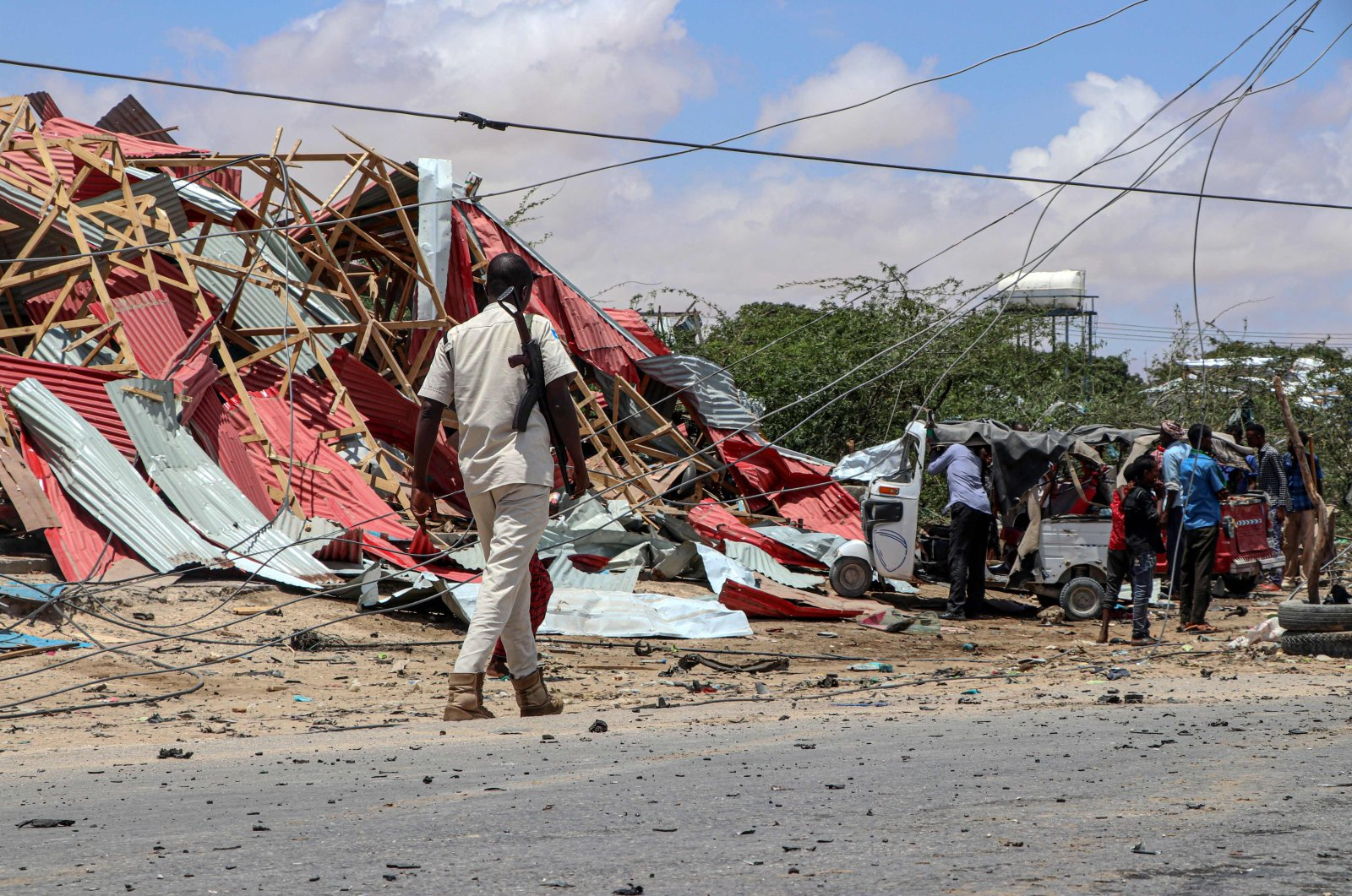 A Somali police officer patrols (L) as bystanders gather at the site of a suicide car bomb explosion which targeted a European Union vehicle convoy in Mogadishu, Somalia, on Sept. 30, 2019. (AFP Photo)