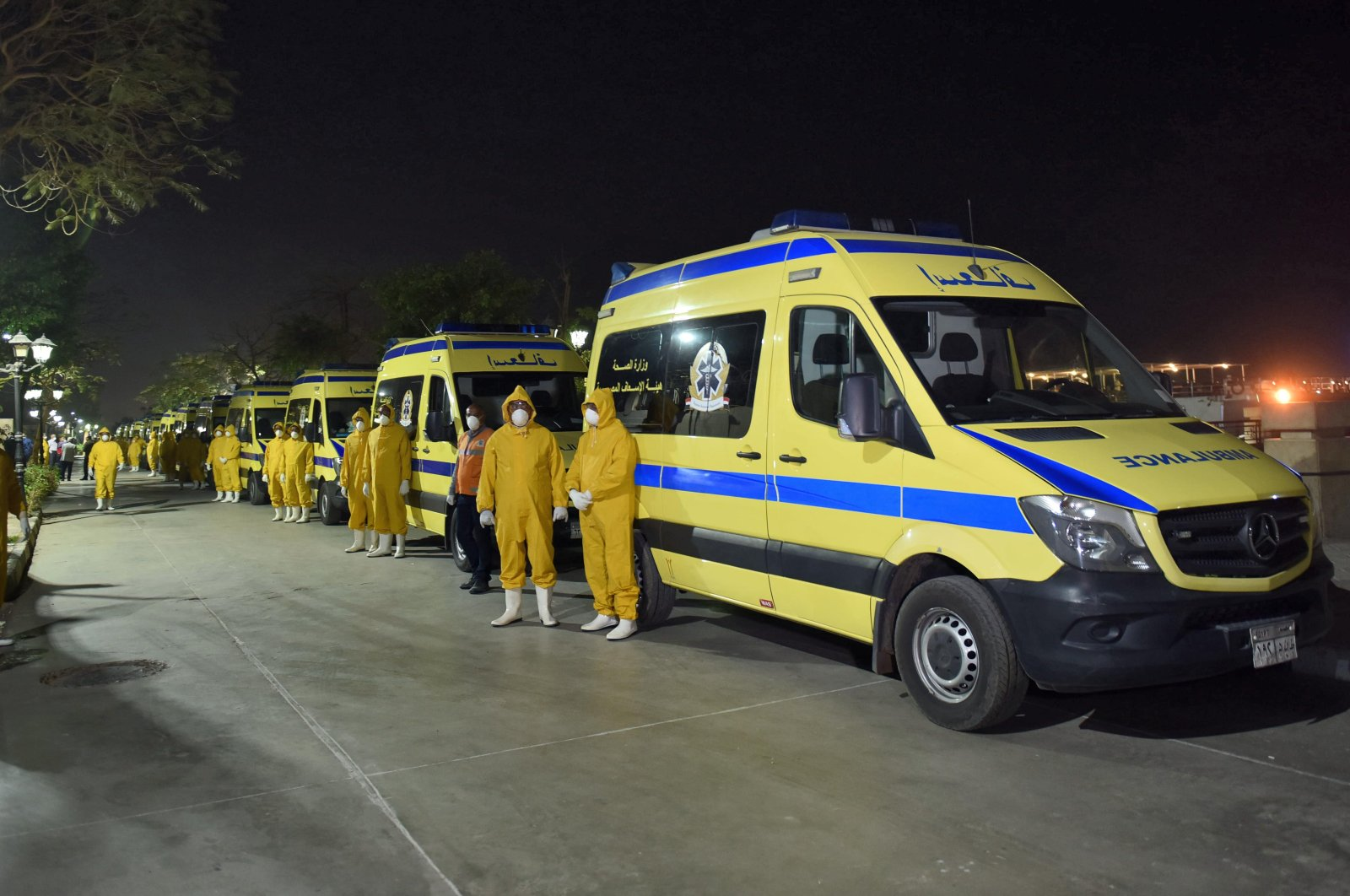 Egyptian health ministry emergency responders stand next to ambulances ready on the scene to transport suspected COVID-19 coronavirus disease cases that were detected on a Nile cruise ship, in the southern city of Luxor late on March 7, 2020. (AFP Photo)