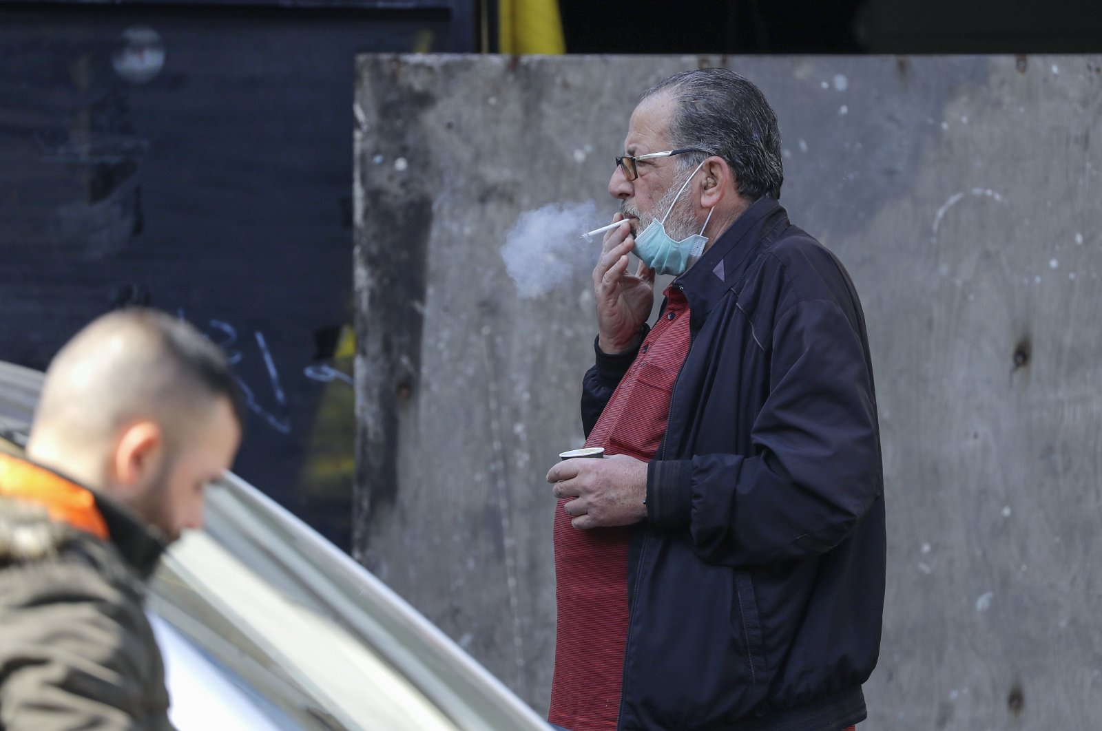 A Lebanese man has his surgical mask lowered to smoke a cigarette on a street of the capital Beirut, on March 2, 2020, amid a novel coronavirus outbreak.(AFP Photo)