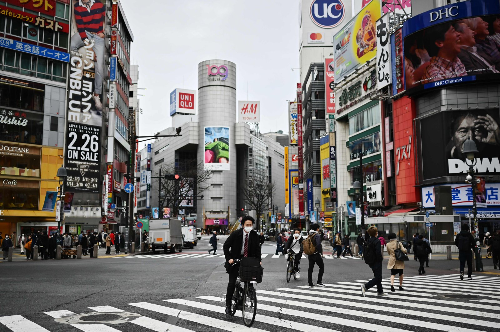 Man wearing a face mask rides a bicycle across a zebra crossing in Shibuya district, Tokyo, March 9, 2020. (AFP Photo)