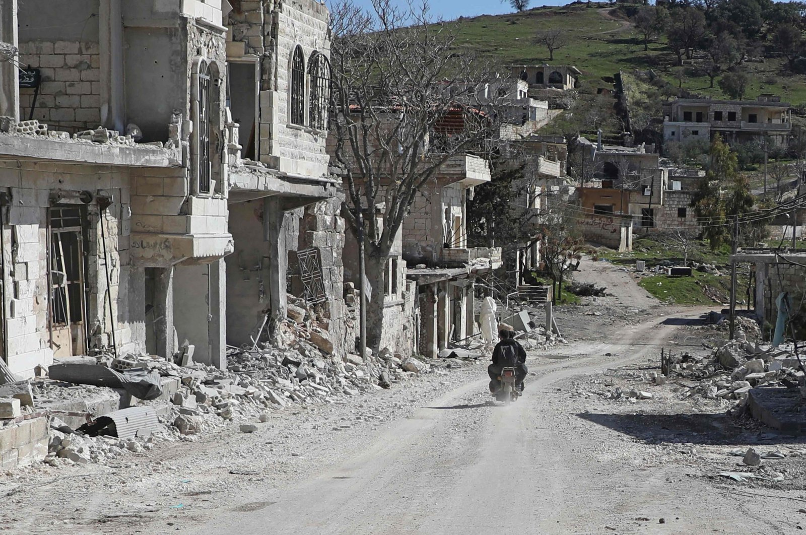 Syrians ride a motorcycle past destroyed buildings in the village of Kafr Oweid in al-Zawiya Mountain region of Syria's northwestern province of Idlib on March 8, 2020, following a Russian-Turkish ceasefire deal. (AFP Photo)
