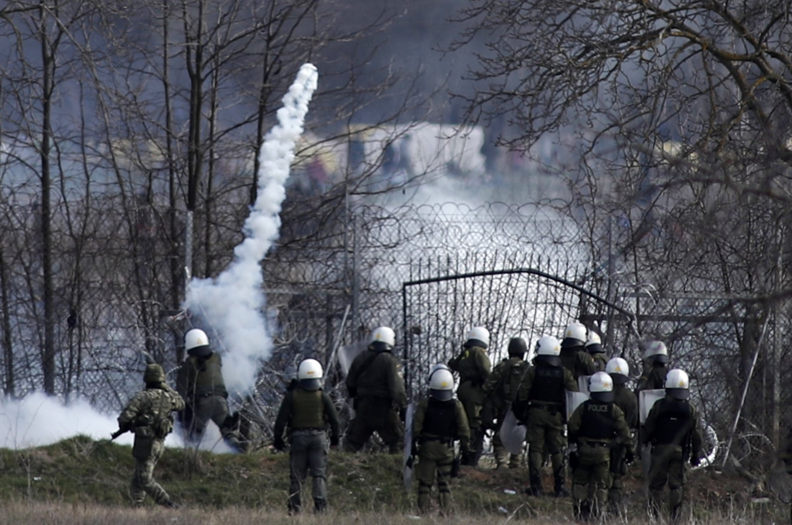 Greek police stand guard as migrants gather at a border fence on the Turkish side during clashes at the Greek-Turkish border in the town of Kastanies, the Evros region, March 7, 2020. (AP Photo)