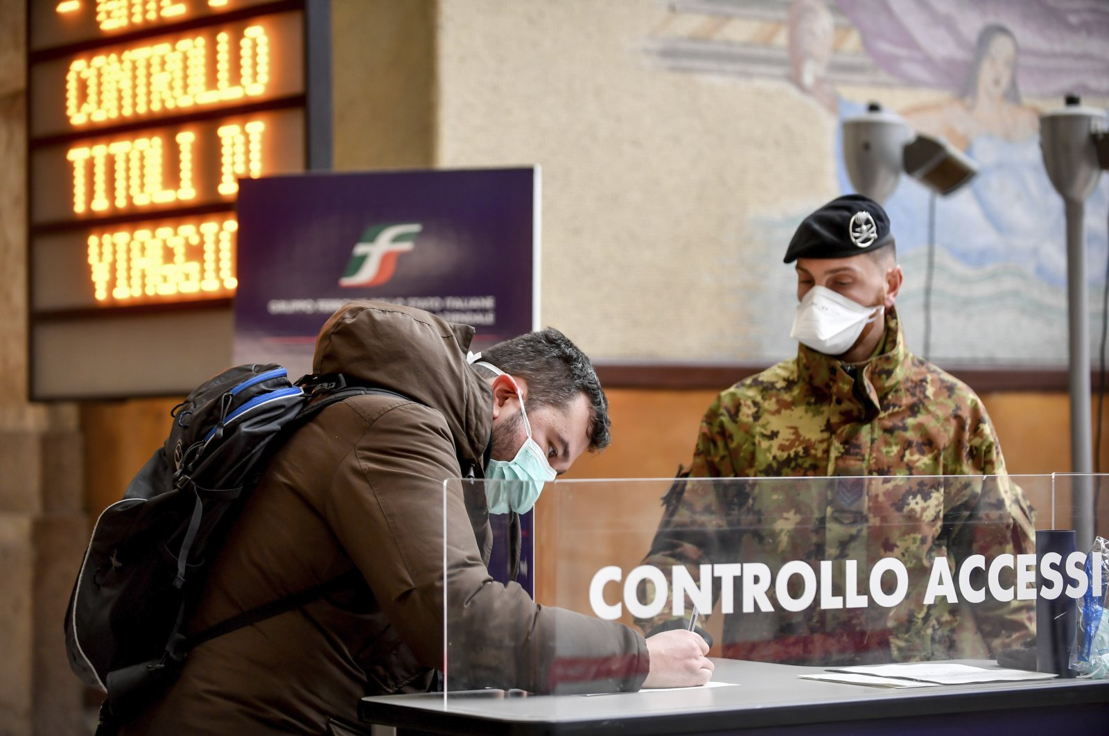 A passenger leaving from Milan Central railway station signs a release form next to a patrolling soldier, Milan, March 9, 2020. (AP Photo)