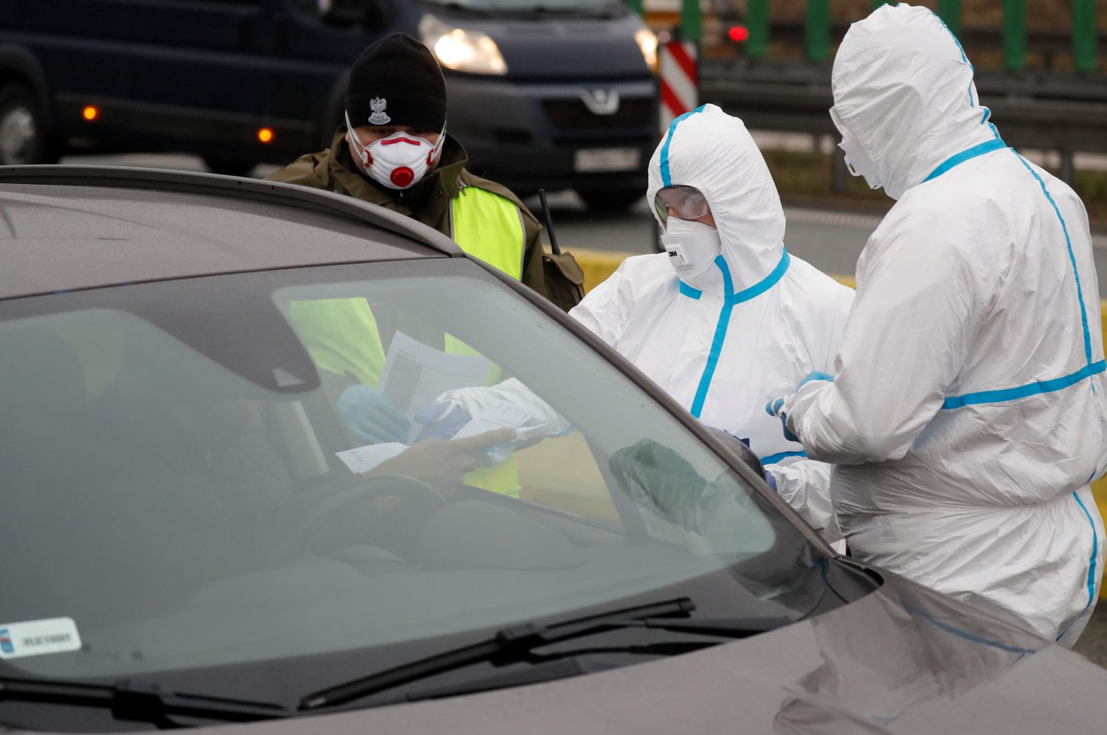 Medical staff with protective clothing perform checks on drivers at Jedrzychowice border crossing, between Poland and Germany, March 9, 2020. (AFP Photo)
