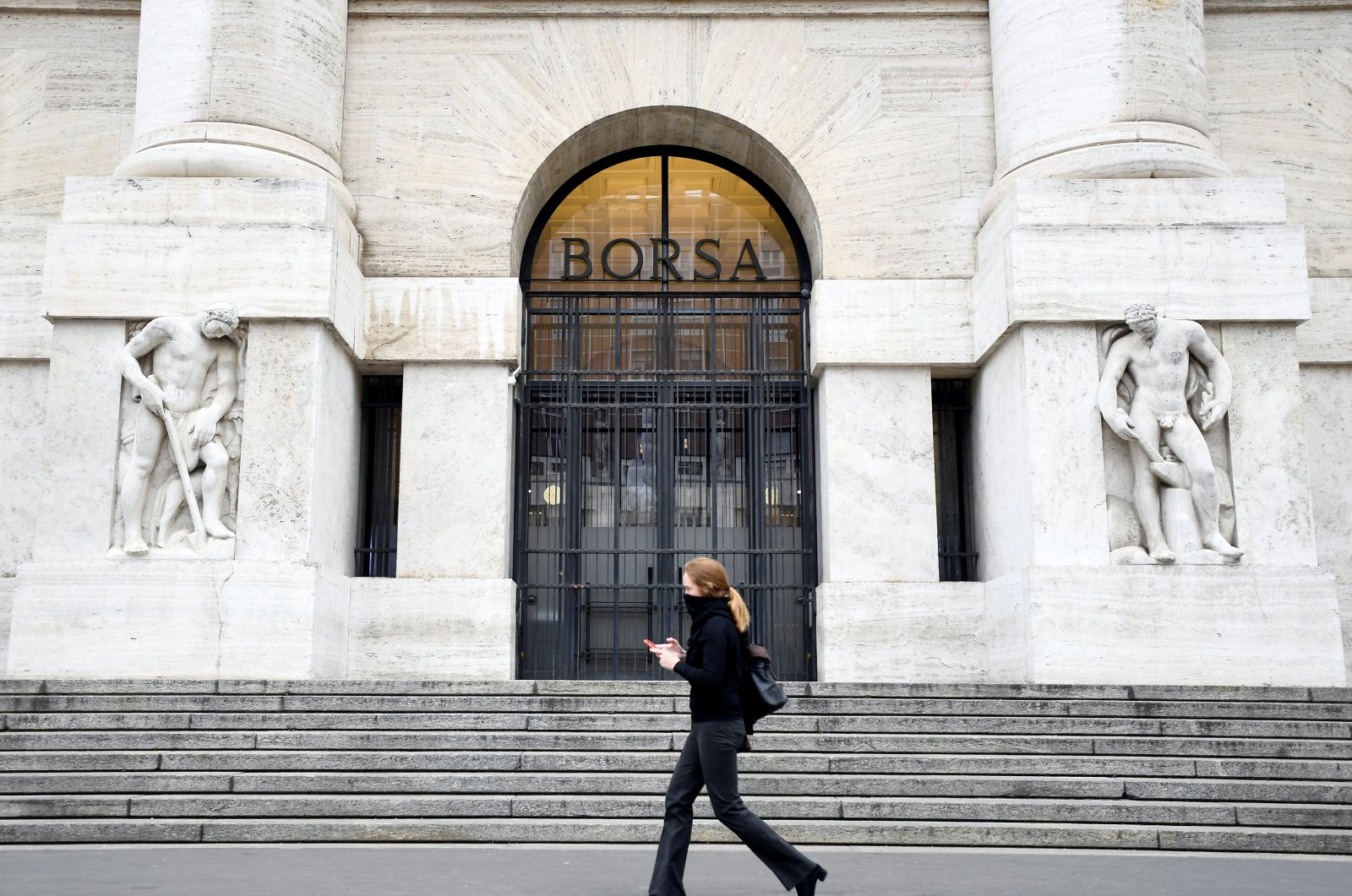 A woman goes past the Italian Stock Exchange, Milan, Feb. 25, 2020. (REUTERS Photo)