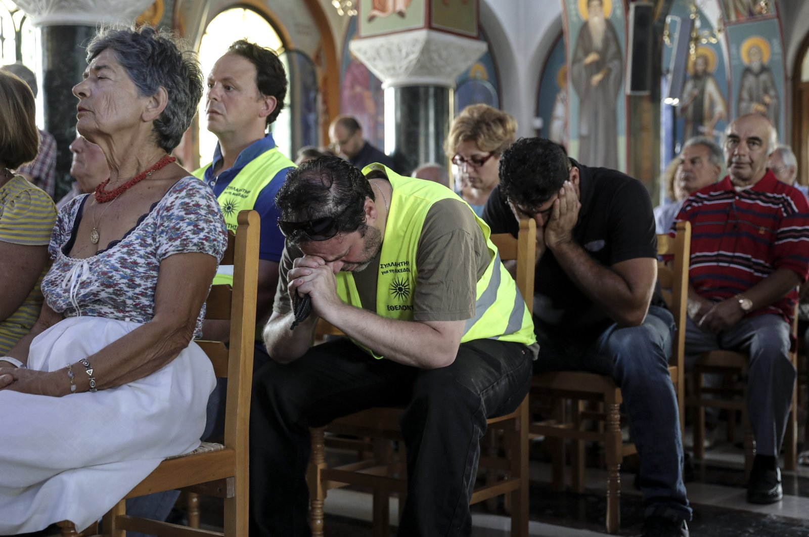 Orthodox faithful attend a memorial service for the victims of a forest fire, inside a church at Mati village, east of Athens, July 29, 2018. (AP Photo)