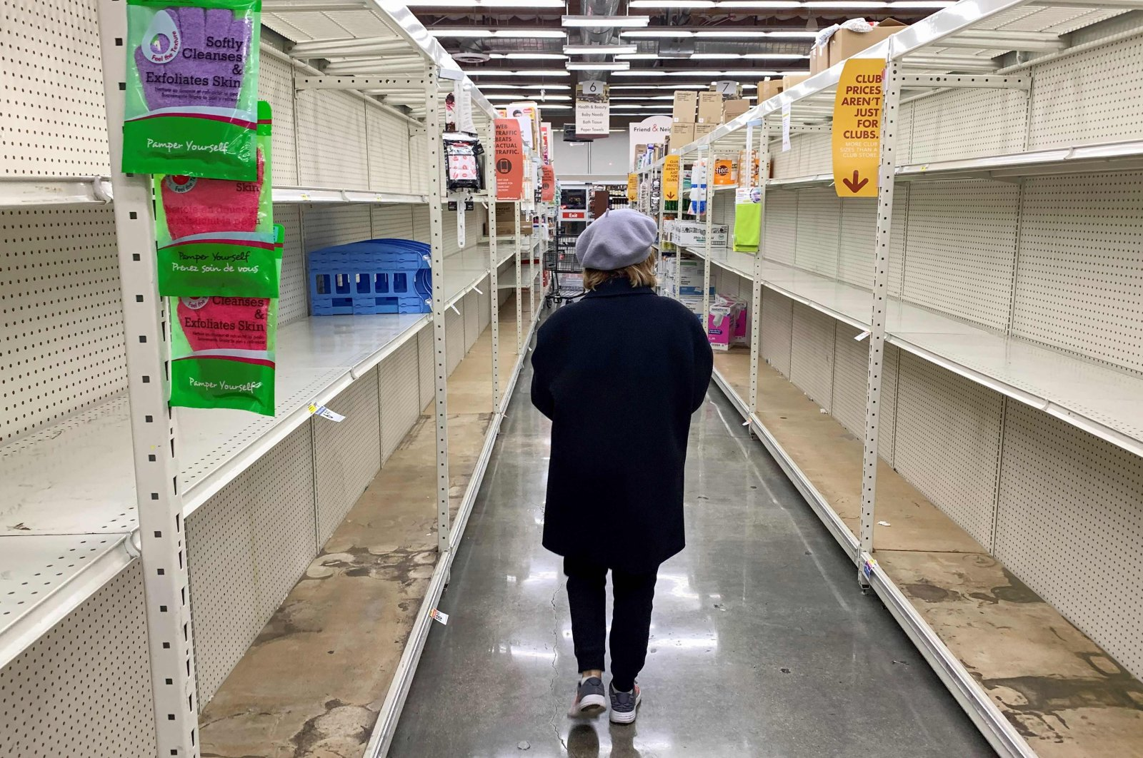 A shopper walks past empty shelves normally stocked with soaps, sanitizers, paper towels, and toilet paper at a Smart & Final grocery store in Glendale, California, March 7, 2020. (AFP Photo)