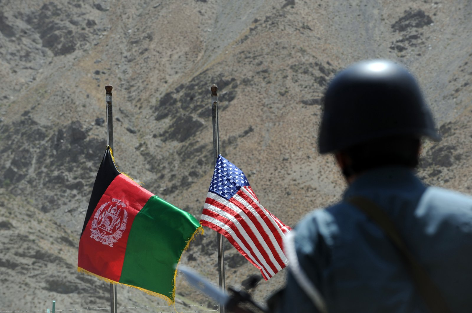 In this file photo taken on July 24, 2011 Afghan and US flags are raised as a policeman keeps watch during a ceremony to hand over security control in the rugged mountains of the Panjshir valley. (AFP Photo)