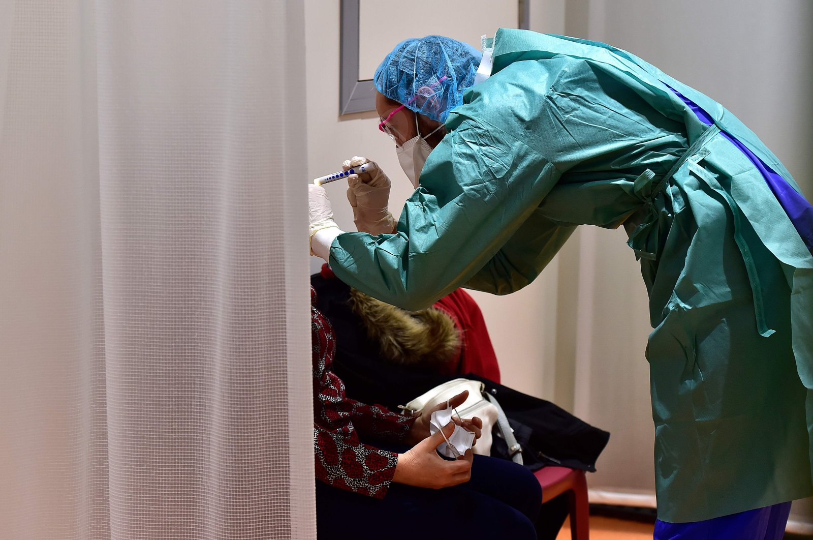 A doctor examines a patient at the hospital screening unit of the CHU Pellegrin in Bordeaux, southwestern France on March 9, 2020. (AFP Photo)