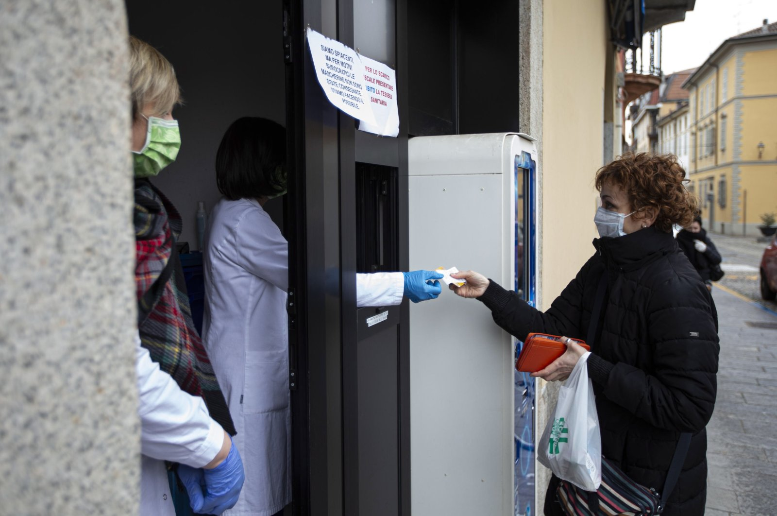 A woman wearing a protective mask gets her drugs in a Pharmacy in Codogno, Italy, 09 March 2020. (EPA Photo)