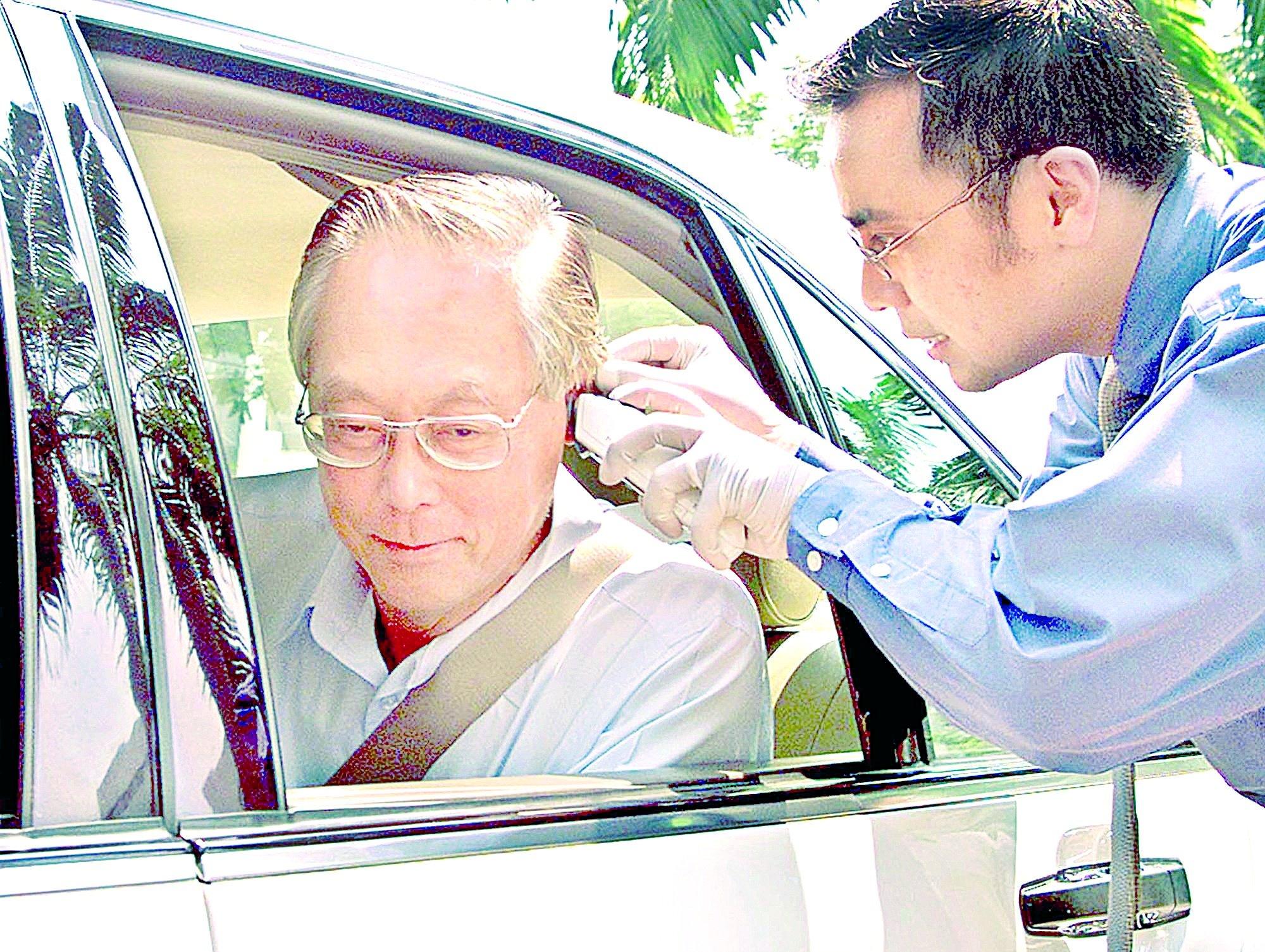 Singapore Prime Minister Goh Chok Tong gets his temperature taken outside of parliament on April 24, 2003. (AP Photo)