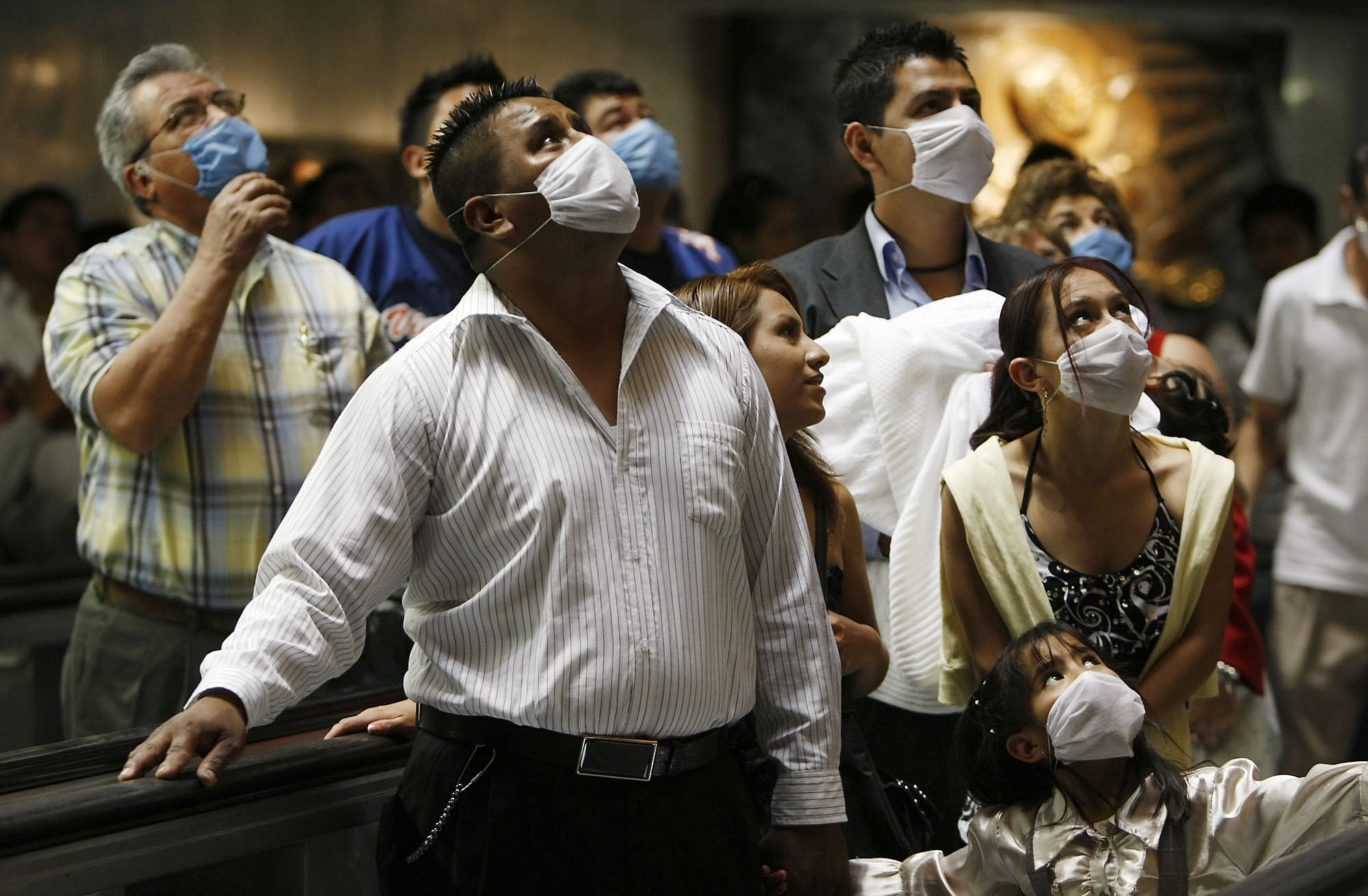 People wearing protective masks pay their respects to Our Lady of Guadalupe as they pass over a walkway under Guadalupe's shrine at the Basilica de Guadalupe in Mexico City, on Sunday, April 26, 2009. (AP Photo)