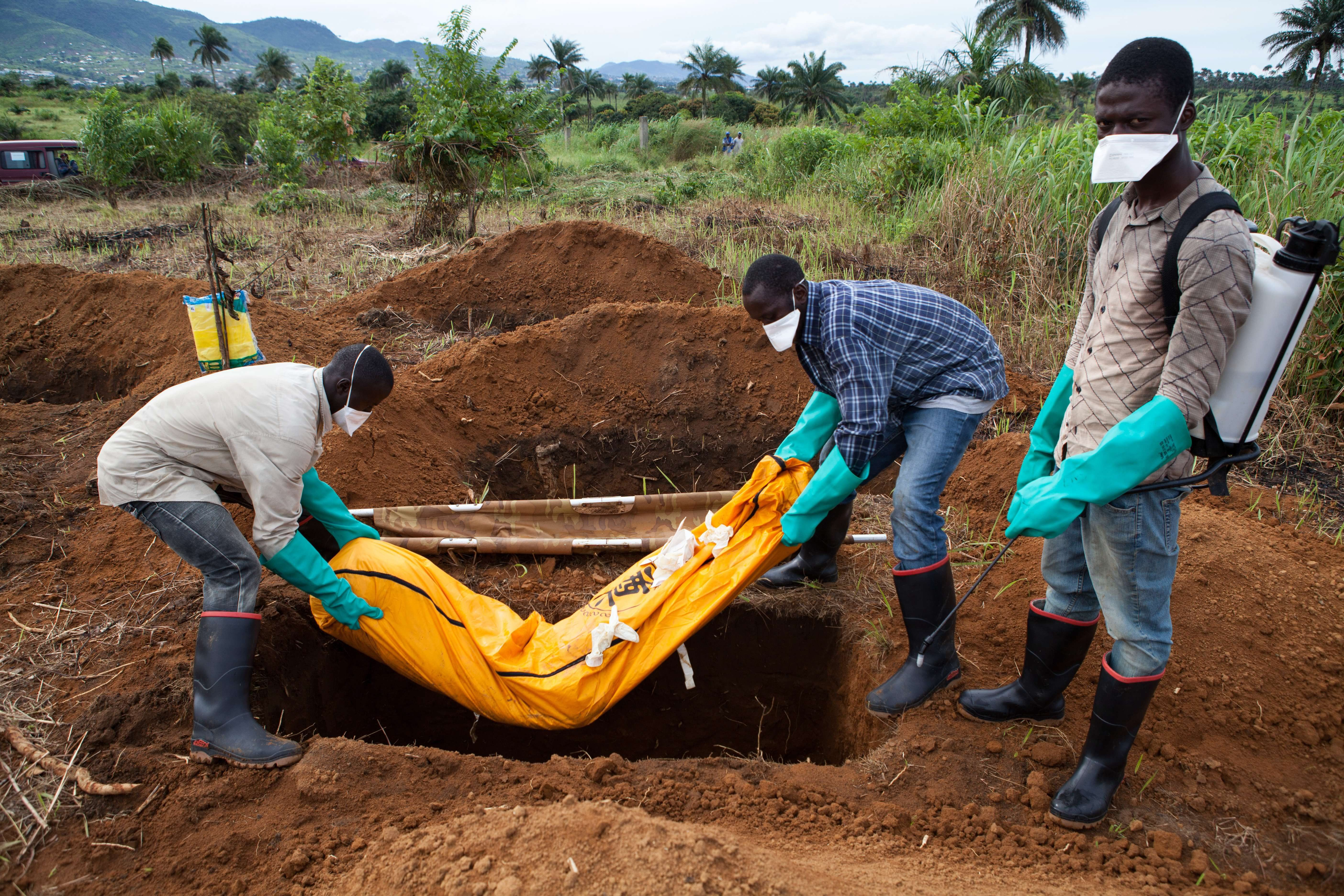 Photo taken on Oct. 7, 2014, shows volunteers in protective suits burying the body of a person who died from Ebola in Waterloo, some 30 kilometers southeast of Freetown, Sierra Leone. (AFP Photo)